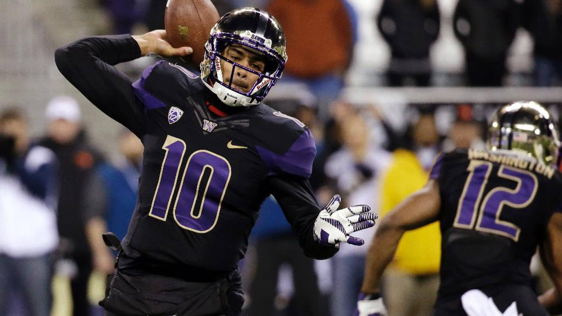 Washington quarterback Cyler Miles drops back to pass against Oregon State in the first of an NCAA college football game Saturday, Nov. 22, 2014, in Seattle. (AP Photo/Elaine Thompson)