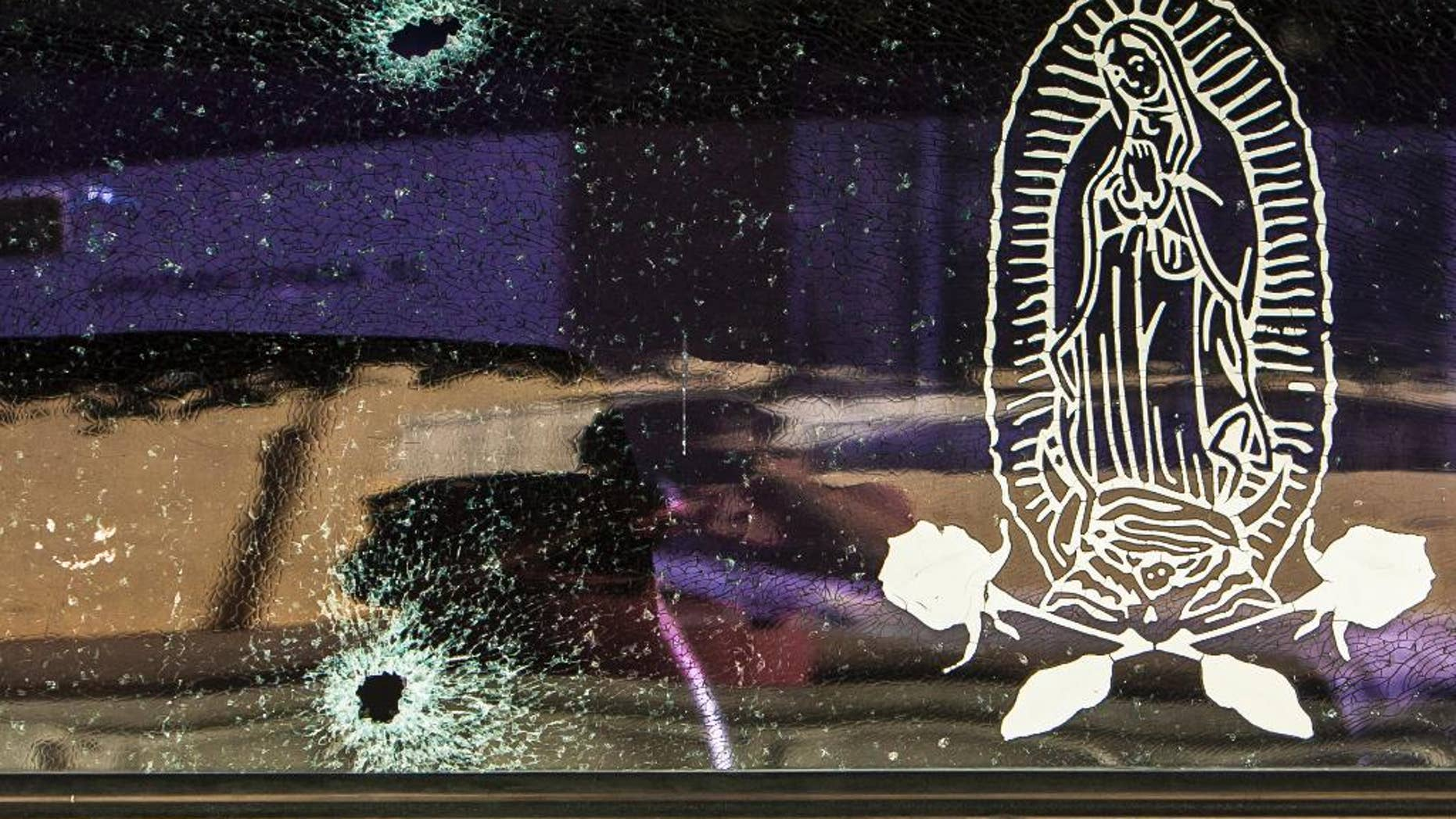The rear windshield of a vehicle is held together by a transparent film with an image of the Virgin of Guadalupe, after being struck by bullets in Culiacan, Mexico, Tuesday, Feb. 7, 2017.(AP Photo/Rashide Frias)