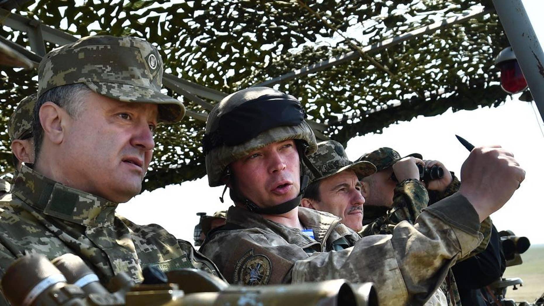 April 25, 2015: Ukrainian President Petro Poroshenko, left, watches a military exercise of the Ukrainian armed forces in Mykolaiv region, Ukraine.