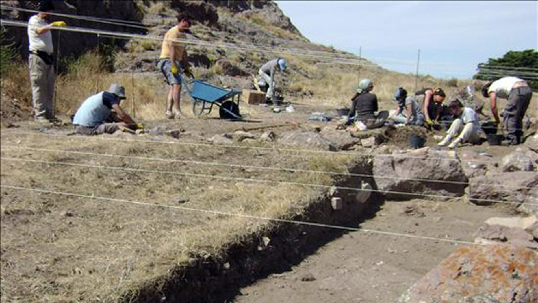 Argentine anthropologists search a lakeside beach, where they found human skeletal remains some 8,270 years old.