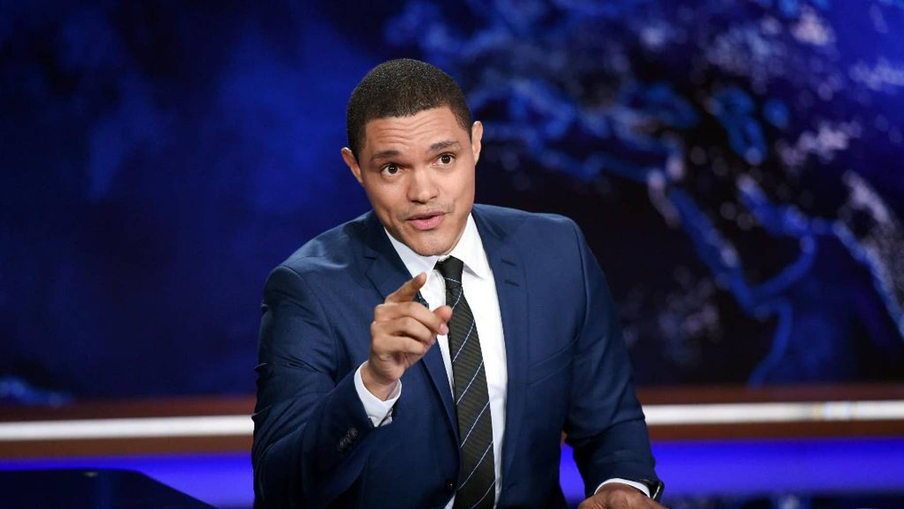 """FILE - In this Sept. 29, 2015, file photo, Trevor Noah works on set during a taping of """"The Daily Show with Trevor Noah"""" in New York. As they returned to work after Sunday morning's mass shooting in a gay nightclub in Orlando, Fla.,, TV's late-night hosts faced the challenge none of them looks forward to. They had to find a way to bond with their viewers, as they do every night, but with shared feelings unrelieved by the comfort of comedy. That is what Noah did Monday, June 13, 2016. (Photo by Evan Agostini/Invision/AP, File)"""