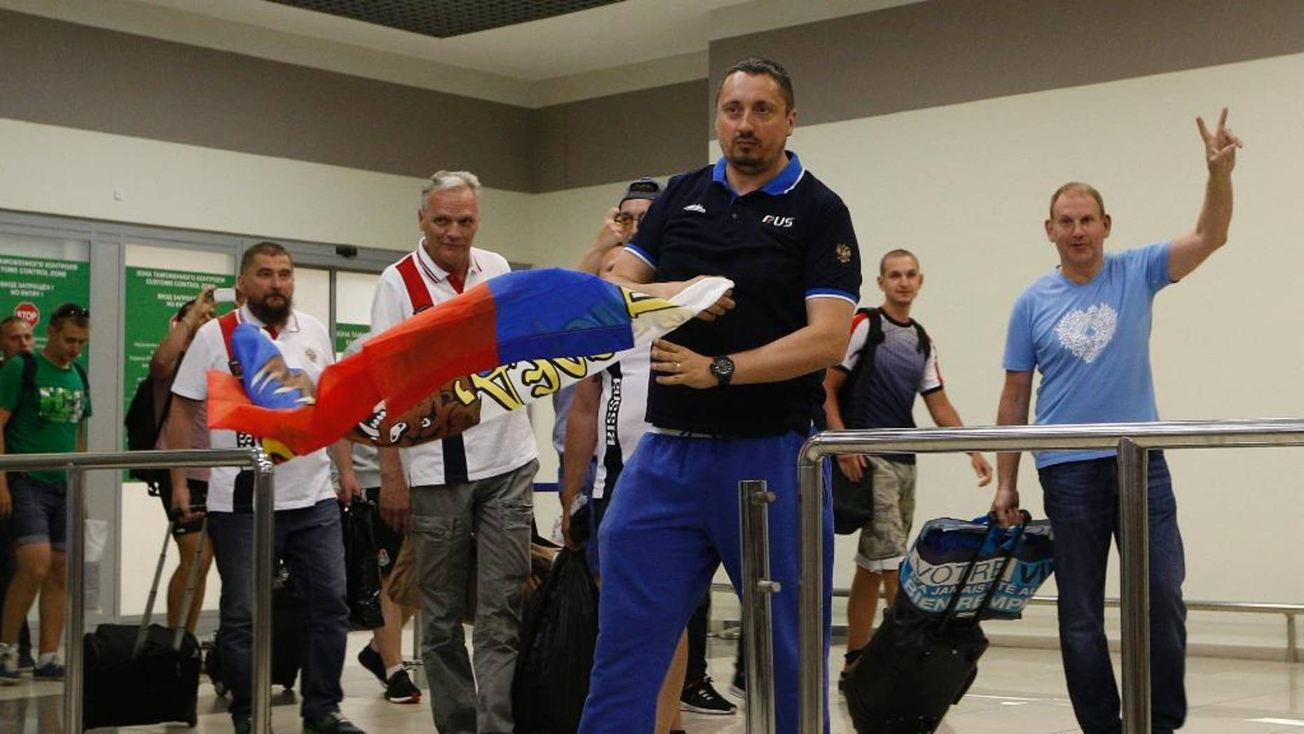 Alexander Shprygin, the leader of a Russian fan group, carries a Russian flag as he with a group of soccer fans deported from France arrived in Moscow, Russia, Saturday, June 18, 2016. A group of 20 Russian soccer fans were deported from France, after French authorities accused them of being involved in hooliganism. (AP Photo/Alexander Zemlianichenko)