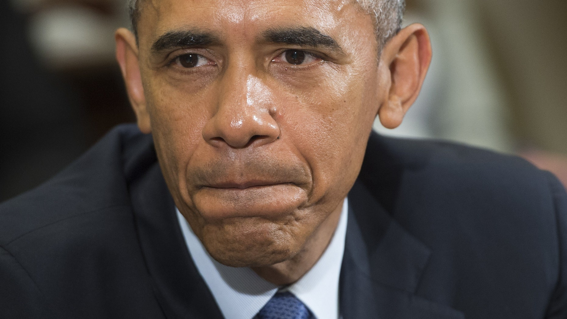 """US President Barack Obama speaks about the report of a video released by the Islamic State depicting the killing of a Jordanian fighter pilot, during an unrelated meeting with Americans who say they have benefited from the Affordable Care Act, commonly known as """"Obamacare,"""" in the Roosevelt Room of the White House in Washington, DC, February 3, 2015. (Photo credit should read SAUL LOEB/AFP/Getty Images)"""
