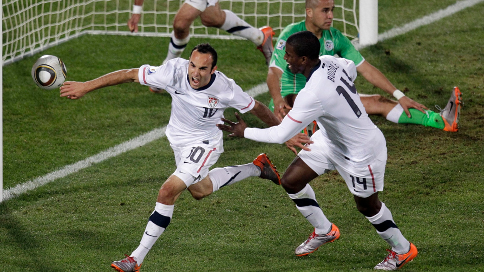 United States' Landon Donovan, front left, celebrates after scoring a goal with fellow team members United States' Clint Dempsey, back left, and United States' Edson Buddle, front right, during the World Cup group C soccer match between the United States and Algeria at the Loftus Versfeld Stadium in Pretoria, South Africa, Wednesday, June 23, 2010.  (AP Photo/Michael Sohn)