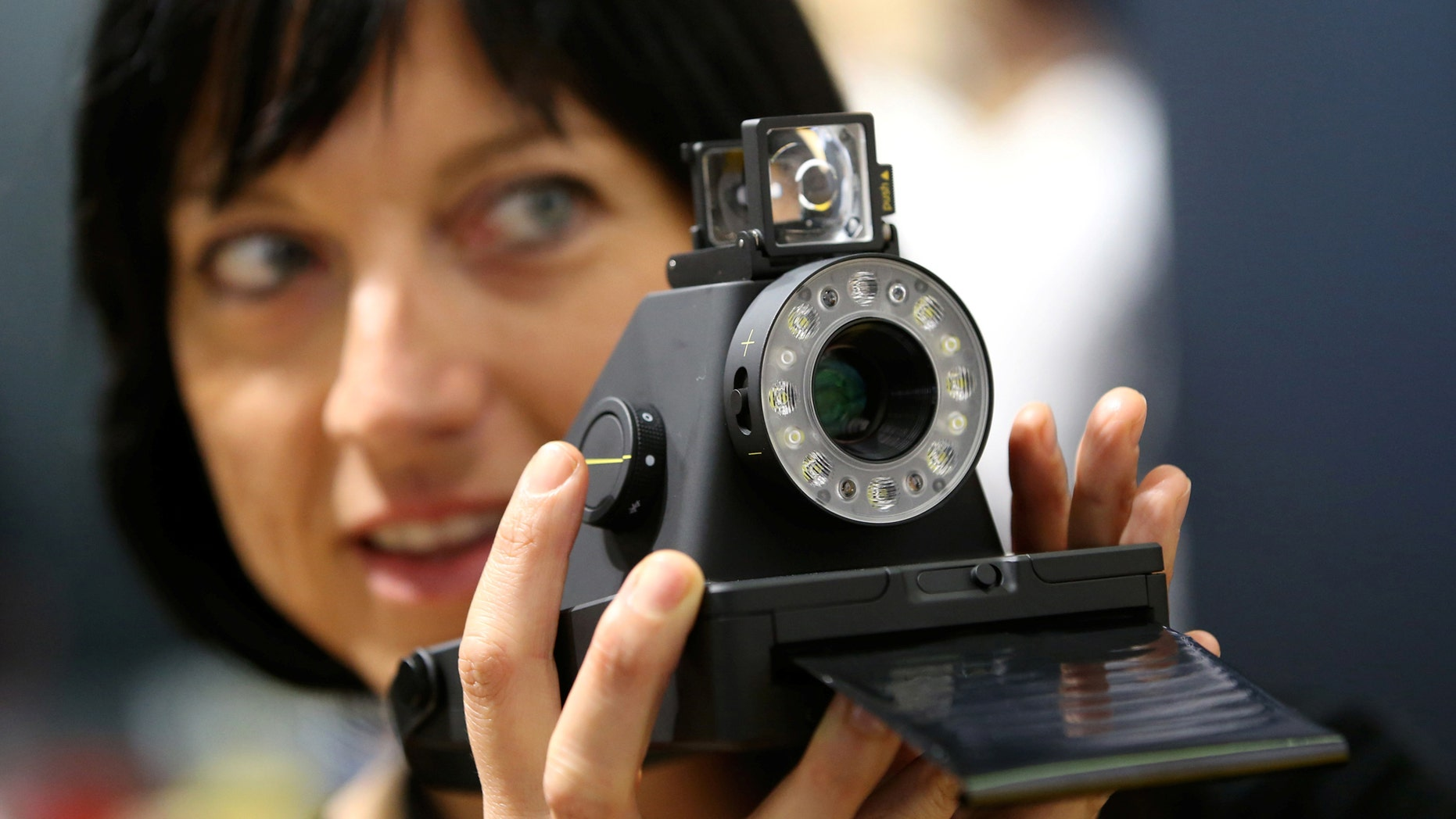 File photo: A woman takes a picture with the Impossible I-1 analog instant camera, the first new camera system working with the original Polaroid photo format, at the booth of the Impossible project on the Photokina, the world's largest fair for imaging in Cologne, Germany, September 20, 2016. (REUTERS/Fabrizio Bensch)