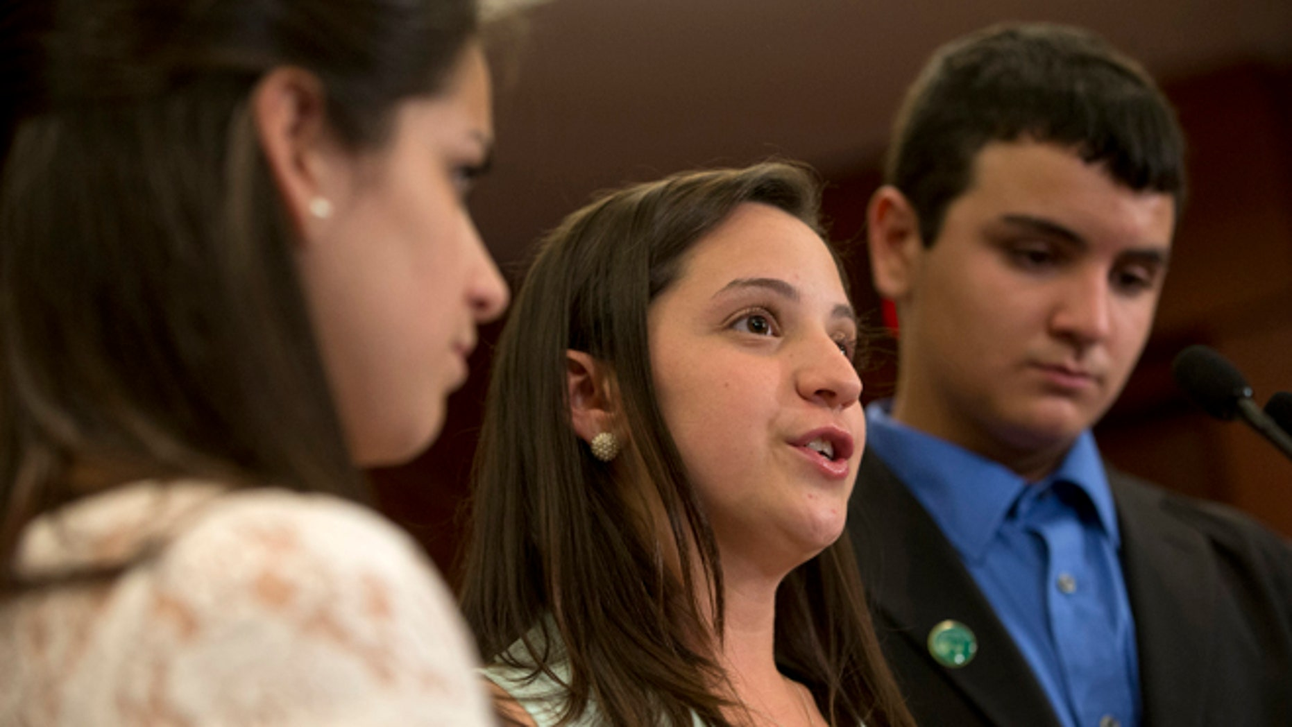 FILE - In a Thursday, June 13, 2013 file photo, Jillian Soto, center, with sister Carlee Soto, left and brother Carlos Soto, the siblings of Victoria Soto, speaks during a news conference on Capitol Hill in Washington, on the sixth month anniversary of the Newtown, Conn. shootings. The family of Victoria Soto, who was killed in the Sandy Hook school massacre, has applied to trademark her name in an attempt to stop others from misusing it on social media. (AP Photo/Jacquelyn Martin, File)