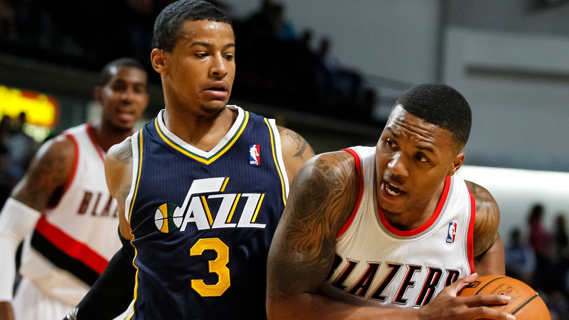 Portland Trail Blazers point guard Damian Lillard, right, drives the ball past Utah Jazz point guard Trey Burke (3) in the first half of a preseason NBA basketball game on Friday, Oct. 11, 2013, in Boise, Idaho. (AP Photo/Otto Kitsinger)