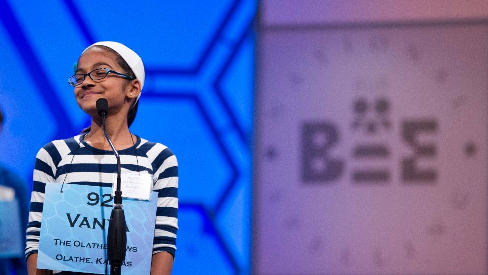 """File-This May 30, 2012, file photo shows Vanya Shivashankar, of Olathe, Kan., smiling as she answers her question during the third round of the National Spelling Bee in Oxon Hill, Md.  Participants and bee officials say the competition is fairer now that kids are tested on what words mean. But it's also taken some of the drama away from the semifinal rounds. Thirteen-year-old Vanya Shivashankar says she misses the simplicity of the old format, which she called """"spelling till you drop."""" Now, there are two semifinal rounds, and test scores determine who makes it to the finals. Vanya was eliminated at that stage last year.  (AP Photo/Evan Vucci, File)"""