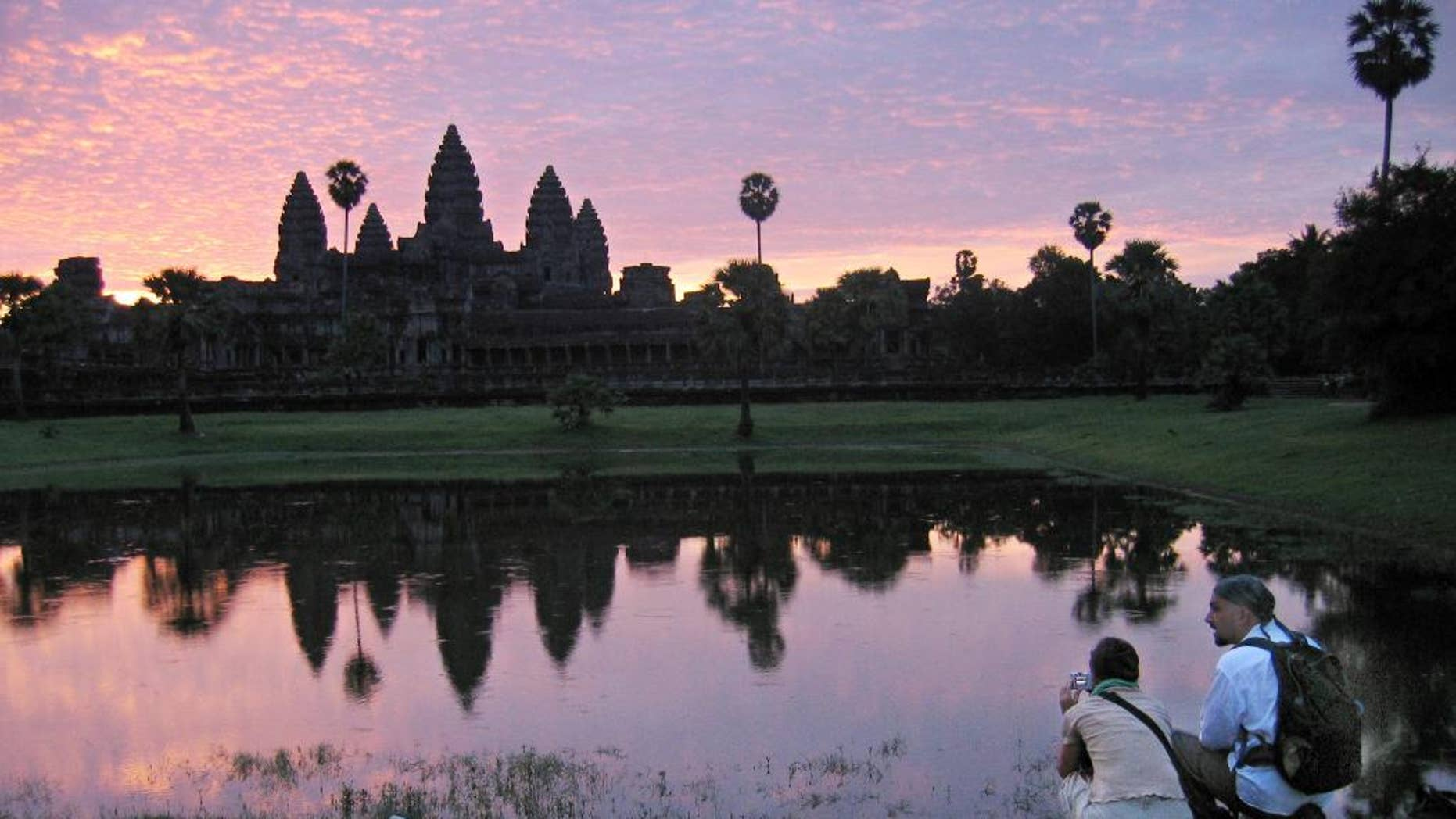 FILE - In this July 14, 2014 file photo, tourists look at the view of the Angkor Wat temples at sunrise, outside Siem Reap, Cambodia. An Australian archeologist says he and colleagues have found evidence of previously undiscovered medieval urban and agricultural networks surrounding the ancient city of Angkor Wat. Using high-tech lasers to scan the Cambodian jungle, Damian Evans and colleagues say they found traces of extensive networks surrounding the monumental stone temple complex at Angkor Wat.  (AP Photo/Anat Givon, File)