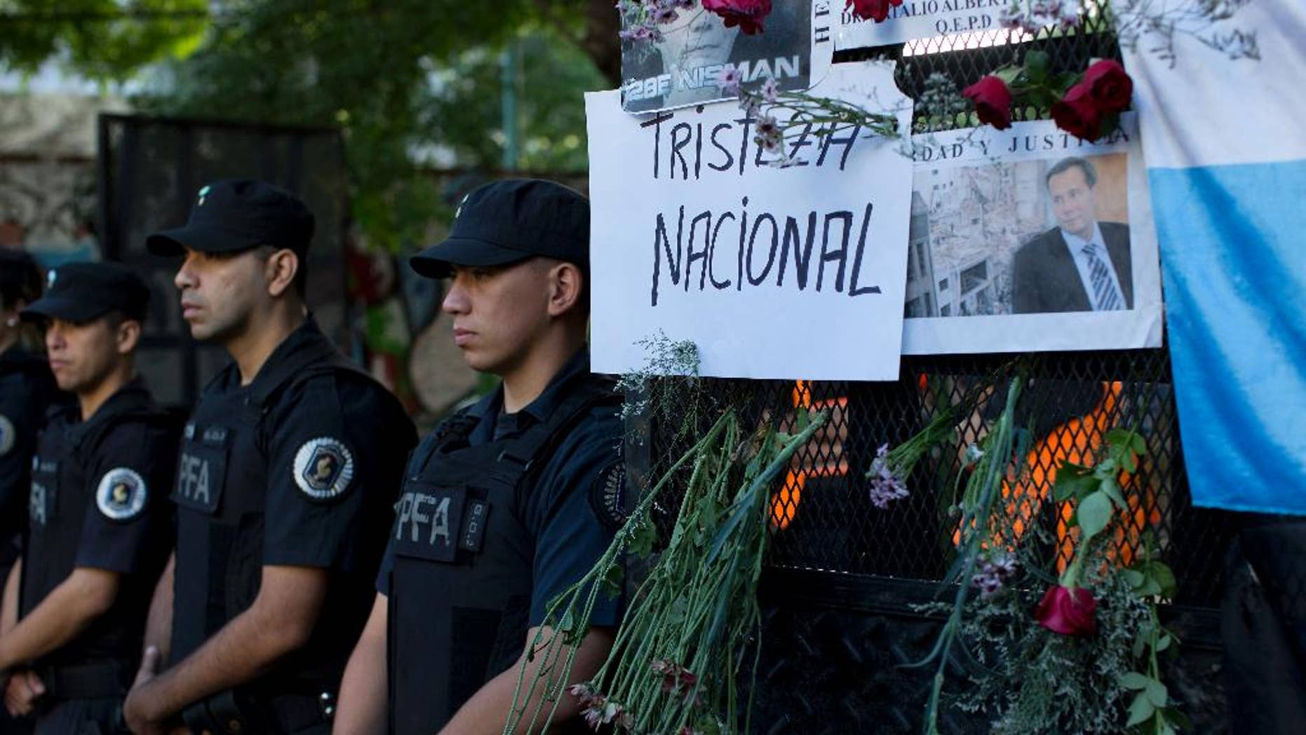 """An image of the late prosecutor Alberto Nisman is taped to a grate next to a hand written sign that reads in Spanish; """"National sadness,"""" outside the funeral home where a private wake was held before the start of the funeral procession, in Buenos Aires, Argentina, Thursday, Jan. 29, 2015. The prosecutor was scheduled to appear before Congress the day after he was found dead in his apartment on Jan. 18, to detail his allegations that President Cristina Fernandez had conspired to protect some of the Iranian suspects in the 1994 bombing of a Jewish center. The man who gave Nisman the gun that killed him said Wednesday that Nisman feared for the safety of his daughters and didn't trust the policemen protecting him. (AP Photo/Rodrigo Abd)"""