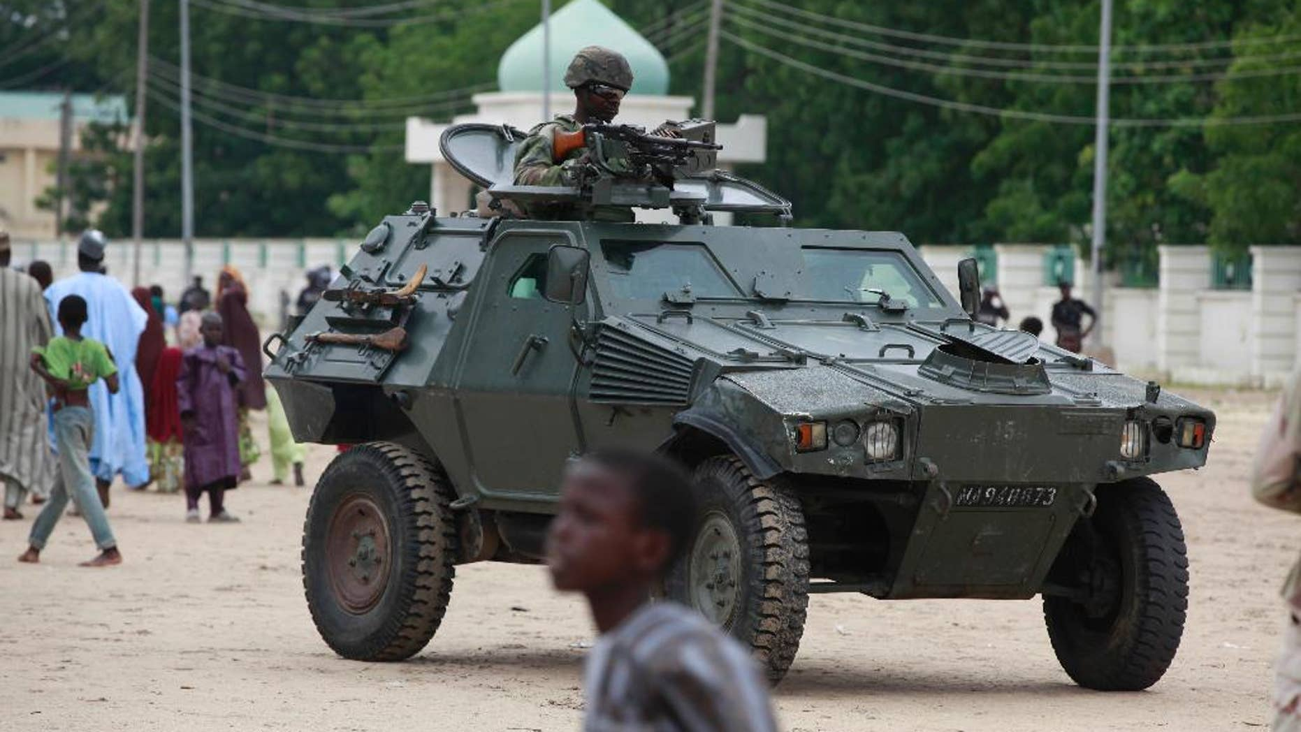 FILE - In this Thursday, Aug. 8, 2013 file photo, Nigerian soldiers ride on an armored personnel carrier during Eid al-Fitr celebrations in Maiduguri, Nigeria. Hundreds of Boko Haram extremists tried to attack the biggest army base in northeast Nigeria overnight but met fierce resistance from soldiers who fired artillery throughout the night. Booming cannon and whooshing rockets woke people living around Giwa Barracks in Maiduguri, the northeast's biggest city. Hundreds fled though some were returning home Thursday, May 14, 2015. Many villagers were killed by shells that hit the outlying village of Kayamla, where the soldiers engaged hundreds of militants, according to Muhammad Gava, a hunter who is secretary of the self-defense Vigilante Group of Nigeria. (AP Photo/Sunday Alamba, File)