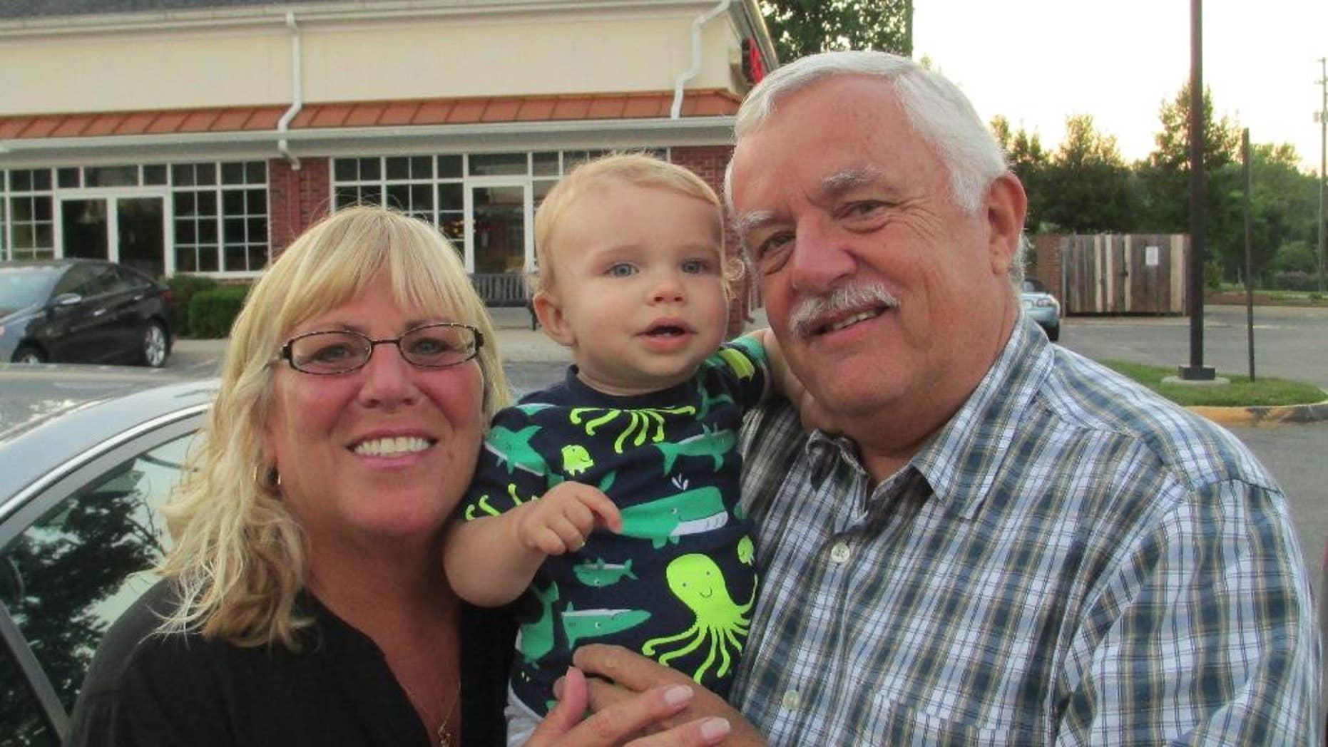 This June 15, 2014 photo provided by the family of Joseph Allen shows one-year-old Joseph Allen, center with his grandparents LuAnn Allen, left, and Herman Allen, right in Richmond, Va. Allen died after a fire broke out at his Midlothian home day care, which was being operated illegally, in 2014. Gov. Terry McAuliffe signed a bill this week that would make it a felony — punishable with up to 10 years in prison — if a child is hurt or killed in a day care that is not properly licensed.  (Matthew Allen via AP)