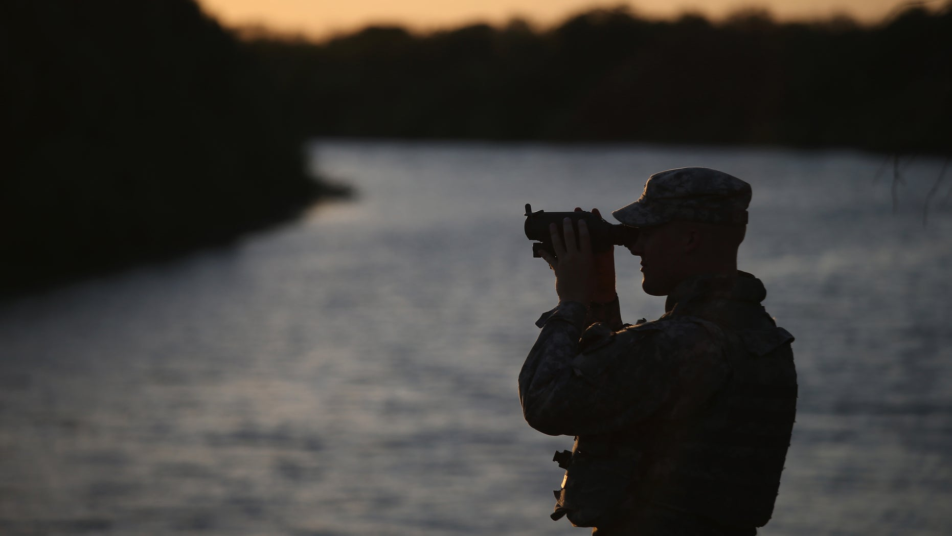 HAVANA, TX - SEPTEMBER 11:  A Texas National Guard soldier scans the Mexican side of the U.S.-Mexico border on September 11, 2014 in Havana, Texas. The troops, deployed along the Rio Grande, are part of a 1,000 strong force called up by Texas Governor Rick Perry to guard the border. The soldiers were sent to help state and federal law enforcement stem a surge of illegal immigrants, many of them families and unaccompanied minors.  (Photo by John Moore/Getty Images)