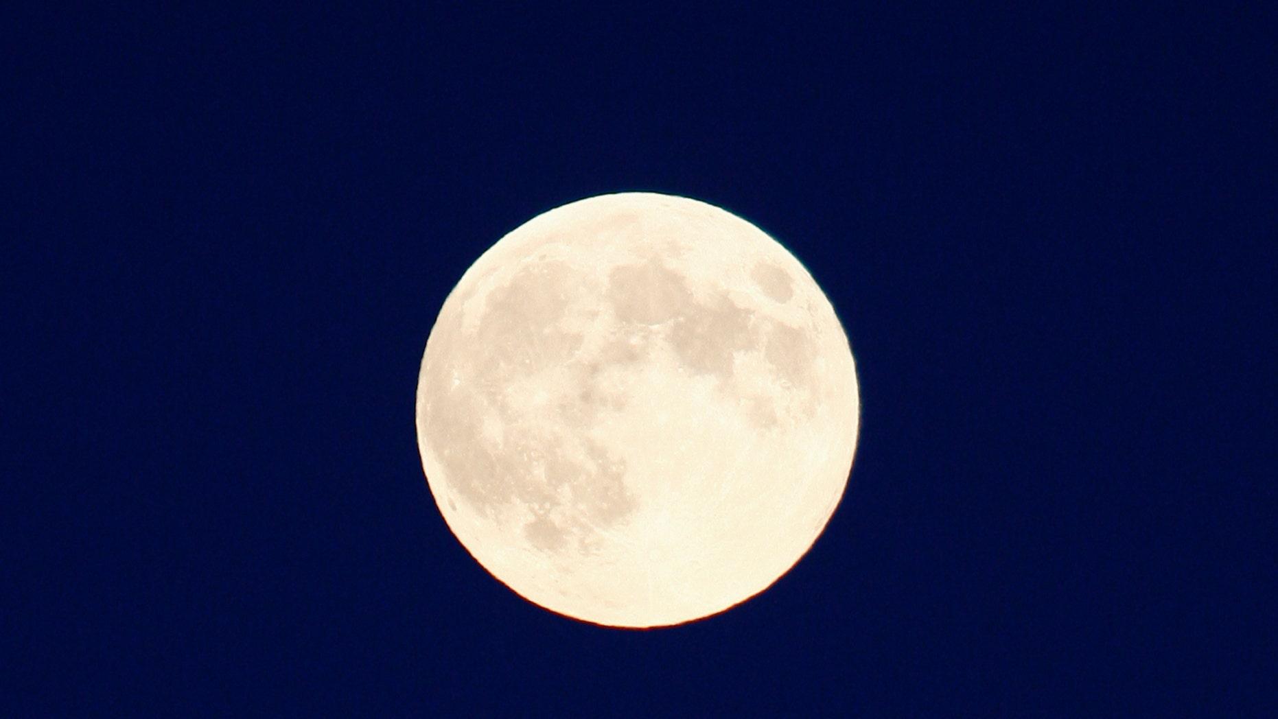A full moon, also a harvest moon, rises over Halton Hills, Ontario outside Toronto, September 8, 2014. (REUTERS/Hyungwon Kang)