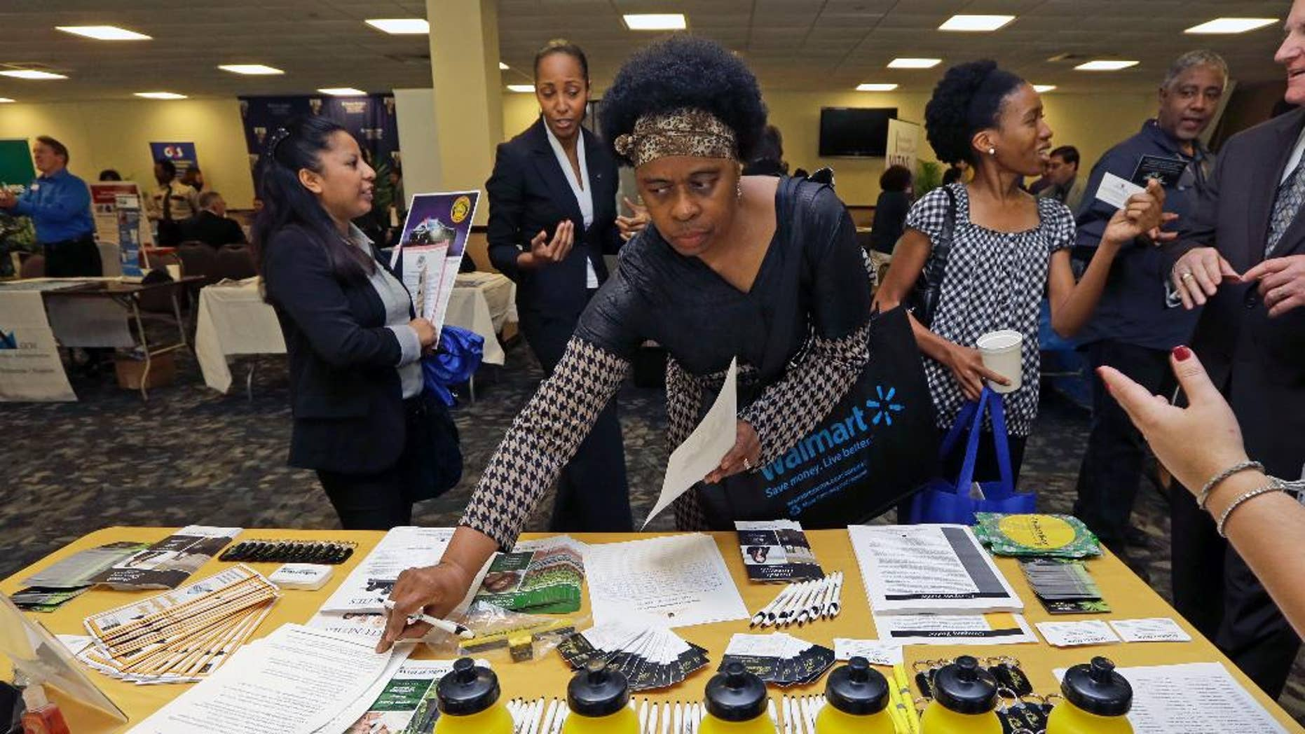 In this photo taken Friday, Feb. 6, 2015, U.S. Army Veteran Fay Belton picks up job information at the annual Veterans Career and Resource Fair in Miami. The U.S. Labor Department reports on the number of people who applied for unemployment benefits for the week ending Feb. 14 on Thursday, Feb. 19, 2015. (AP Photo/Alan Diaz)