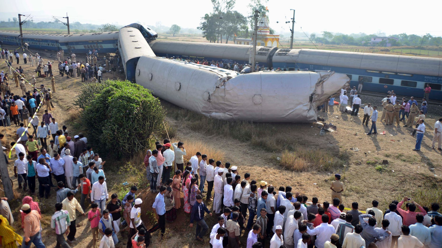 Indian people gather at the site of a train accident near Nashik, 165 kilometers (100 miles) north of Mumbai, India, Friday, Nov. 15, 2013. Police say the passenger train derailed in western India, killing at least two people and injuring another 25. The cause of the accident was not immediately known. (AP Photo)