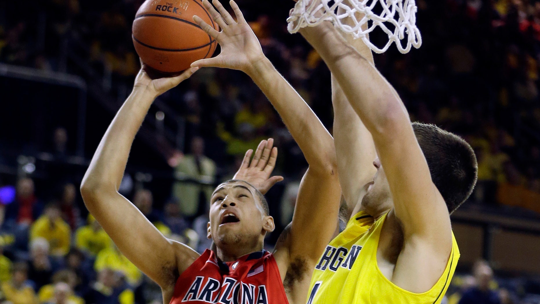 Arizona forward Brandon Ashley (21) makes a lay-up defended by Michigan forward Mitch McGary (4) during the second half of an NCAA college basketball game in Ann Arbor, Mich., Saturday, Dec. 14, 2013. (AP Photo/Carlos Osorio)