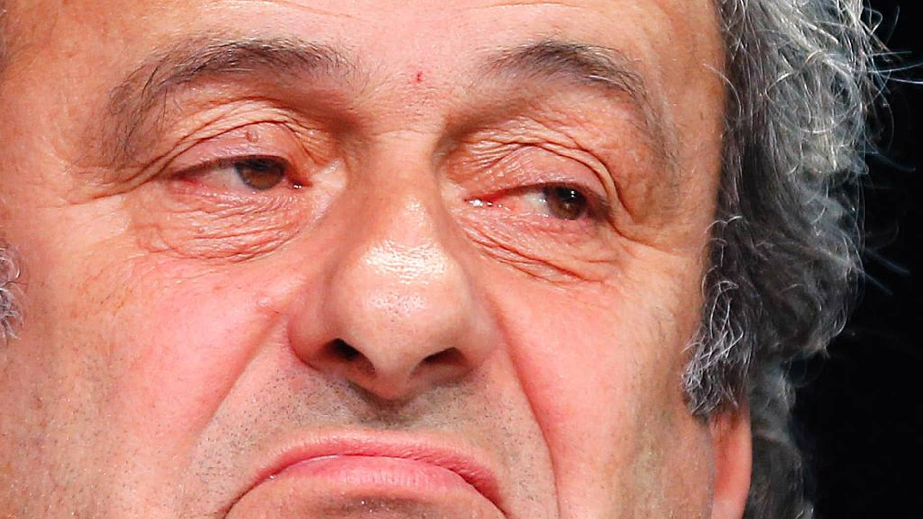 """FILE - In this May 28, 2015 file photo President of UEFA Michel Platini grimaces during a press conference following a meeting of the UEFA board ahead of the FIFA congress in a hotel in Zurich, Switzerland. Complaining that he is being """"dragged through the mud"""" in the FIFA corruption investigation, Michel Platini believes he is """"bullet proof"""" and has not lost support in his bid to replace Sepp Blatter as the head of world soccer's governing body. The UEFA president, who has been suspended for 90 days along with Blatter, confirmed in an interview published Monday, Oct. 19, 2015 in the French daily Le Monde that he had no written contract for the $2 million payment he received from FIFA in 2011. (AP Photo/Michael Probst, File)"""