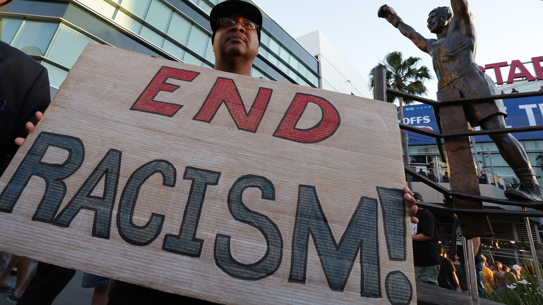 LOS ANGELES, CA -  APRIL 29:   Dexter McLeod holds a sign protesting racist comments made by L.A. Clippers owner Donald Sterling outside Staples Center before a playoff game on April 29, 2014 in Los Angeles, California. Clippers owner Donald Sterling was banned for life today by the NBA and barred from having any association with the team and ordered to pay a $2.5 million fine. (Photo by Jonathan Alcorn/Getty Images)