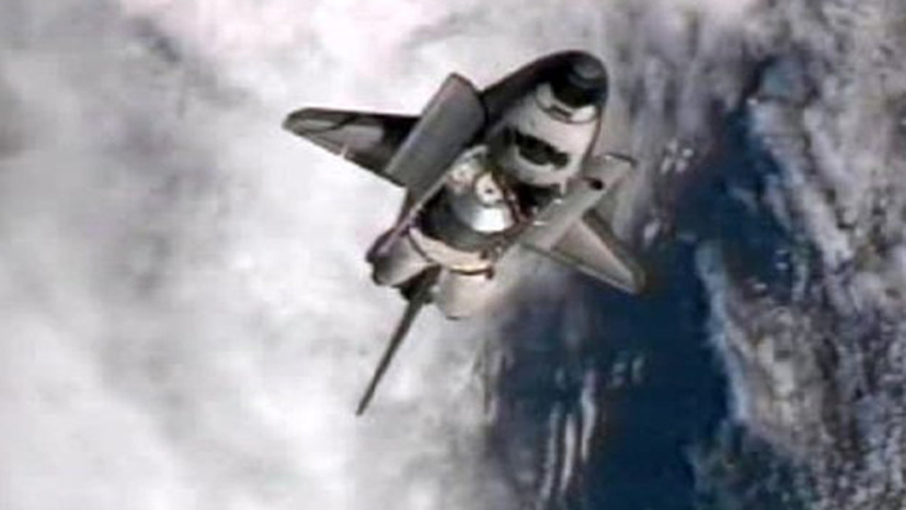 July 10: This frame grab from NASA-TV shows space shuttle Atlantis performing a pitch maneuver as it closes in for one last docking at the International Space Station.