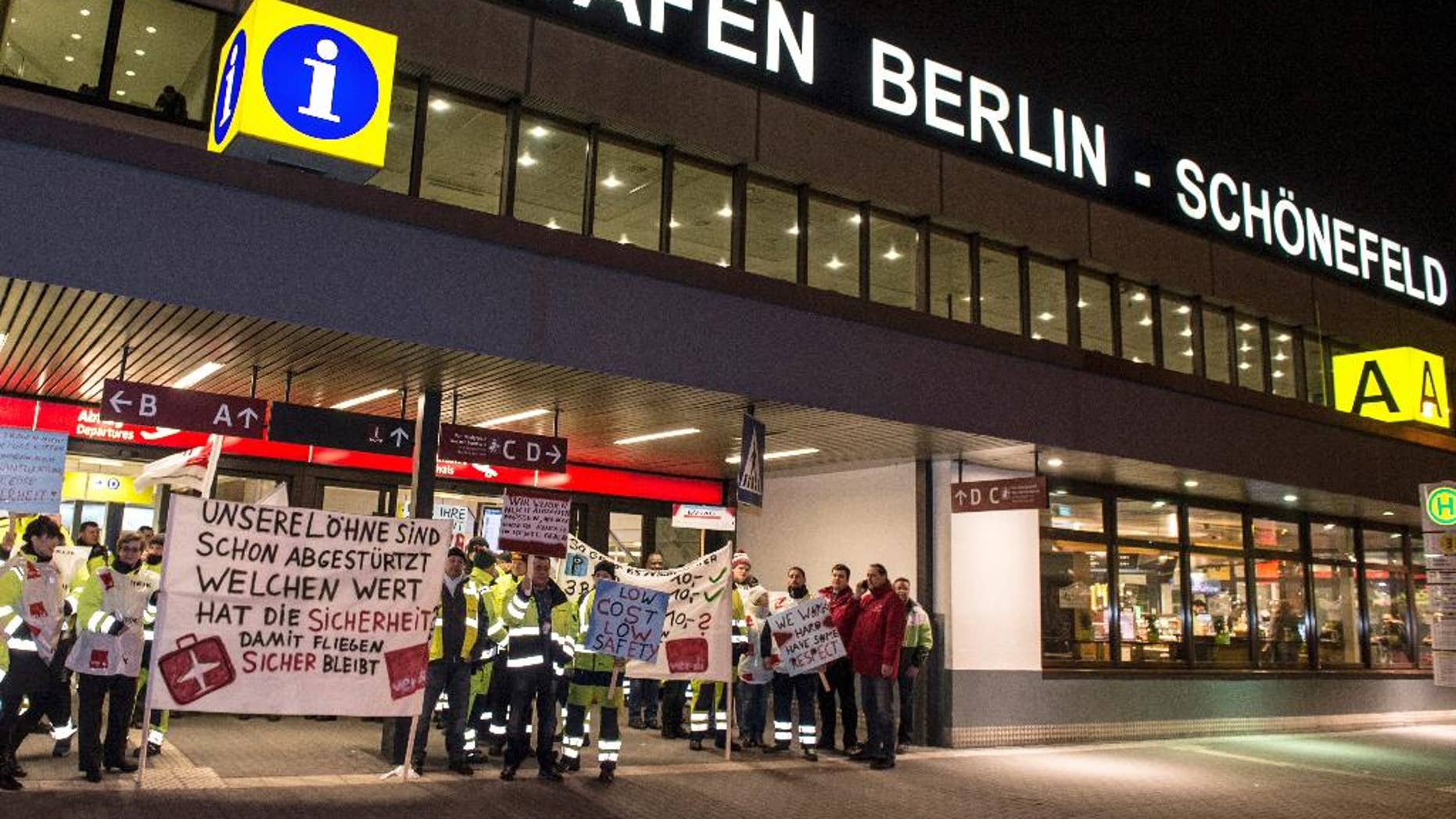 FILE - In this Feb. 8, 2017 file photo, members of the airport ground staff stand at Schoenefeld airport in Berlin, during a warning strike. A union representing ground staff has called on its members to go on strike at Berlin's two airports and warned the walkouts might lead to delays and perhaps flight cancellations. The ver.di union says the strikes would begin Friday at 4 a.m. (0300 GMT) and end Saturday at 5 a.m. (0400 GMT) at the German capital's Tegel and Schoenefeld airports. (Paul Zinken/dpa via AP)