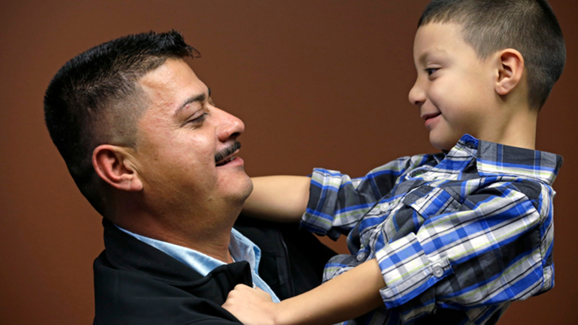 In this photo taken Friday, Oct. 17, 2014, Ignacio Lanuza-Torres holds his son, Isaiah, 4, as he has his photo taken in Seattle. A U.S. Immigration and Customs Enforcement attorney forged a document in an attempt to deport Lanuza-Torres, an immigrant seeking to stay in the country with his wife and children, according to a new lawsuit. The lawsuit, filed Thursday, Oct. 23, 2014, in a Seattle U.S. District Court, seeks $500,000 in damages for Ignacio Lanuza-Torres because the forgery cost him years of courtroom battles and uncertainty over his future. (AP Photo/Elaine Thompson)