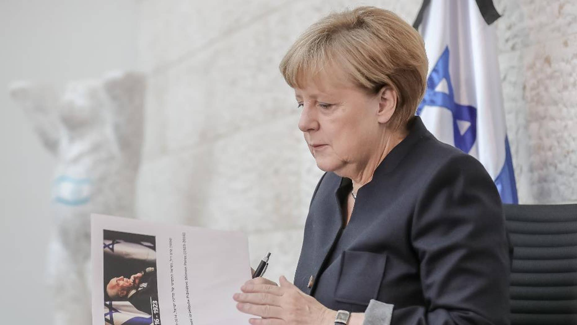 German Chancellor Angela Merkel prepares to sign the book of condolence for former Israeli President Shimon Peres at the embassy of Israel in Berlin, Germany, Friday, Sept. 30, 2016. (Michael Kappeler/Pool Photo via AP)