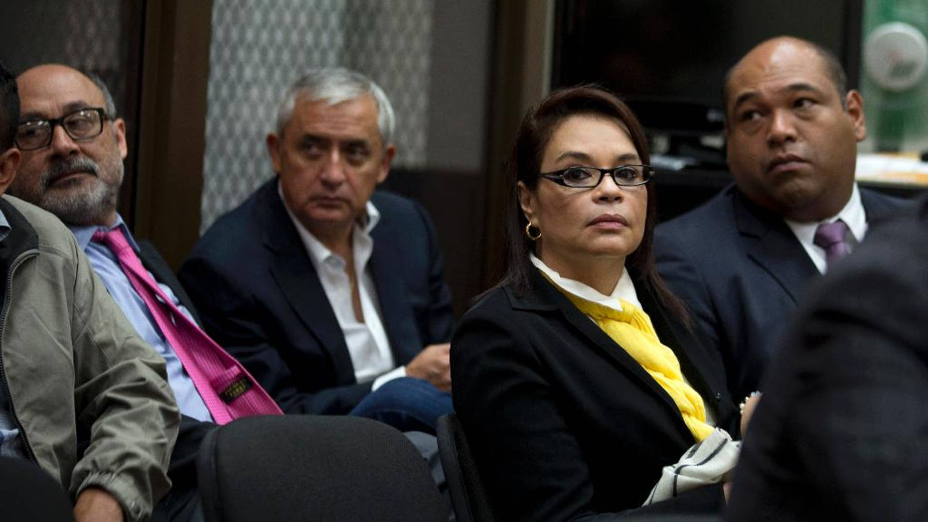 FILE - In this April 20, 2016, file photo, Guatemala's former Vice-President Roxana Baldetti, wearing a yellow scarf, and former President Otto Perez Molina, back center, wait for the start of a court hearing in Guatemala City. Perez and Baldetti have been formally charged on Thursday, June 16, 2016, in a sprawling corruption scheme that emptied government coffers and laundered money to be spent on Miami shopping sprees, real estate and luxury vehicles. (AP Photo/Moises Castillo, File)