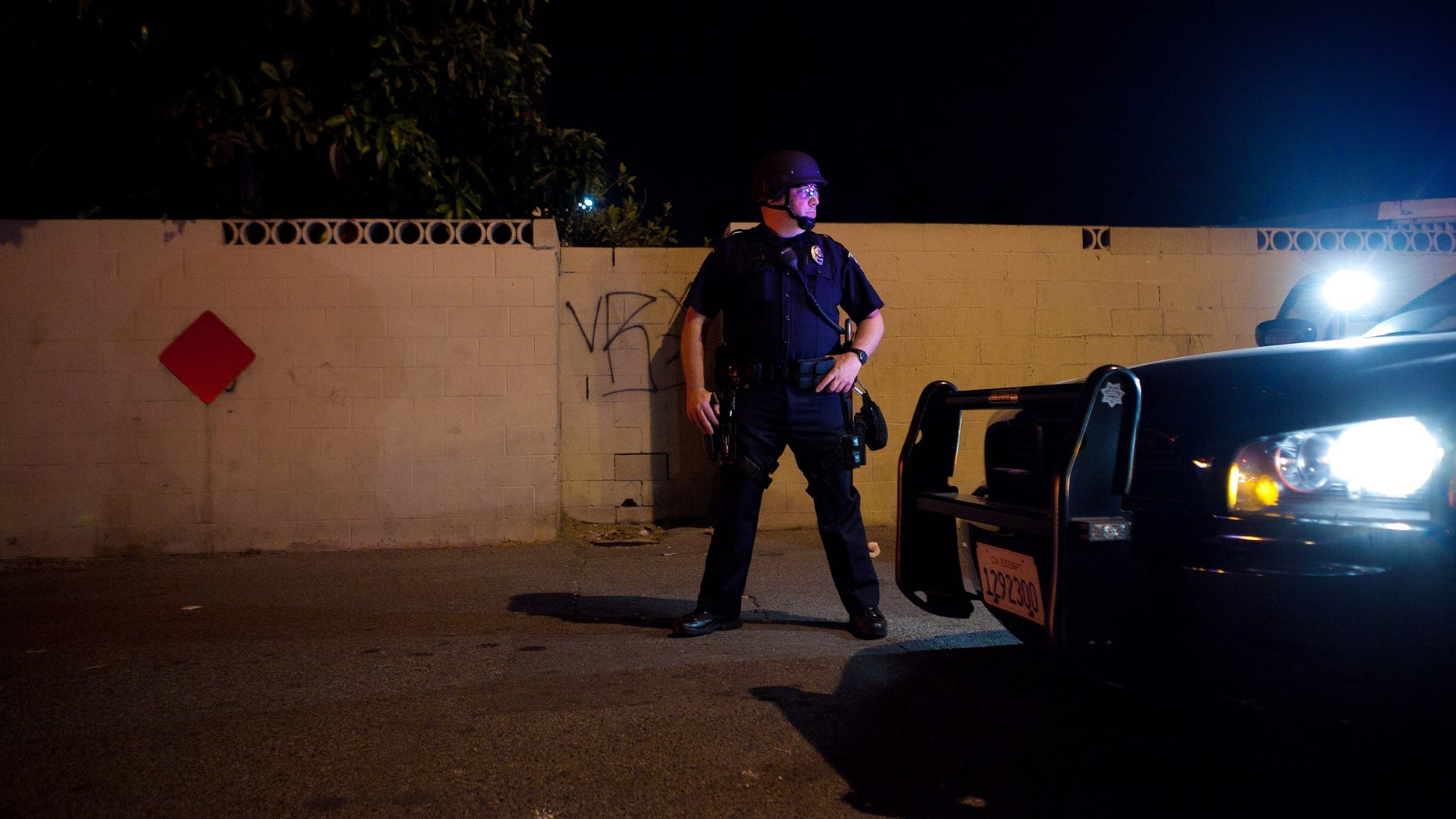ANAHEIM, CA - JULY 25: A police officer stands guard after protesters set fire to a near by trash bin during a demonstration to show outrage for the fatal shooting of Manuel Angel Diaz, 25, at Anaheim City Hall on July 24, 2012 in Anaheim, California. Diaz was fatally shot on July 21 by an Anaheim police officer and has sparked days of protests by the angered community. (Photo by Jonathan Gibby/Getty Images)