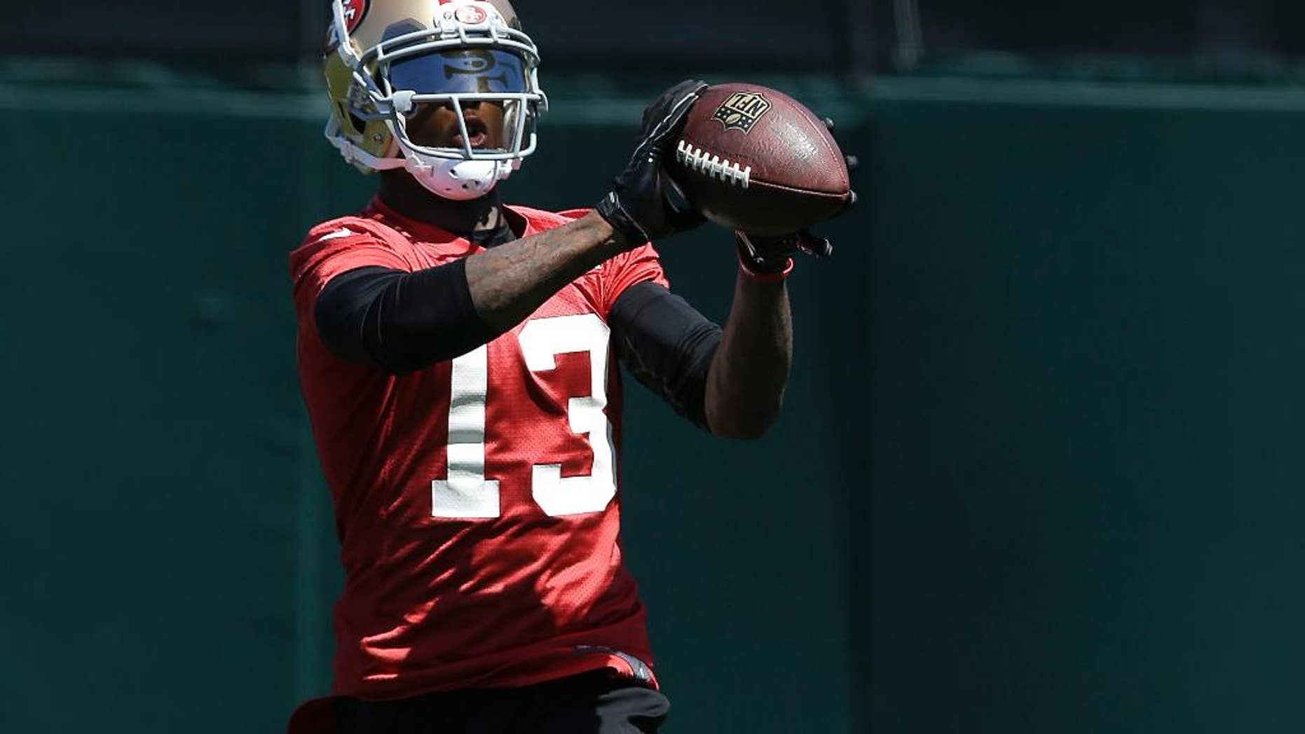 FILE - In this June 17, 2014 file photo, San Francisco 49ers wide receiver Stevie Johnson (13) catches a pass during NFL football minicamp in Santa Clara, Calif. Johnson had produced three straight 1,000-yard seasons with 23 touchdown catches as Buffalo's most dynamic player in the passing game when that streak ended in frustrating fashion last year. There were injuries and the unexpected death of his mother. Now he has a chance to start a new streak with his new team, back home in the Bay Area. AP Photo/Jeff Chiu, File)