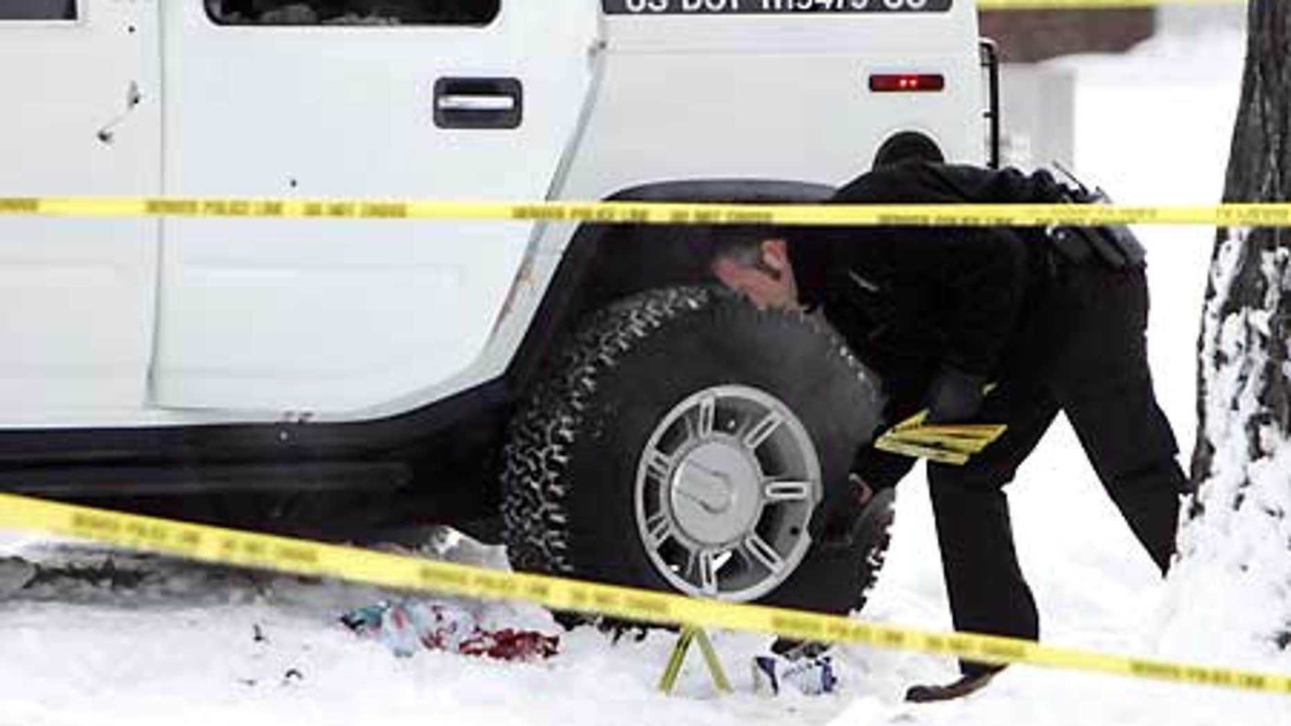 Jan. 1, 2007: An investigator with the Denver Police Department places evidence markers next to the Hummer limo in which Darrent Williams was killed.