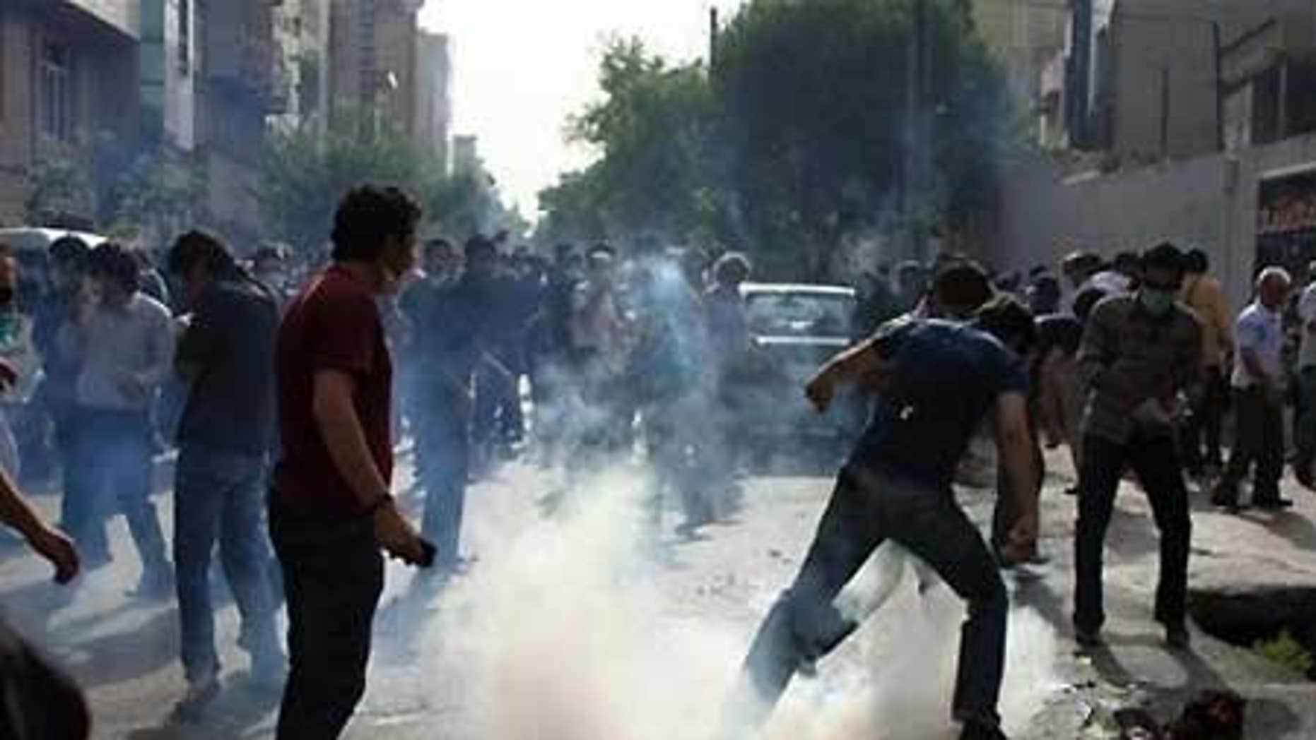 Iranian protestors protect themselves by the fire from tear gas in Tehran, July 9, amid the post-election chaos.