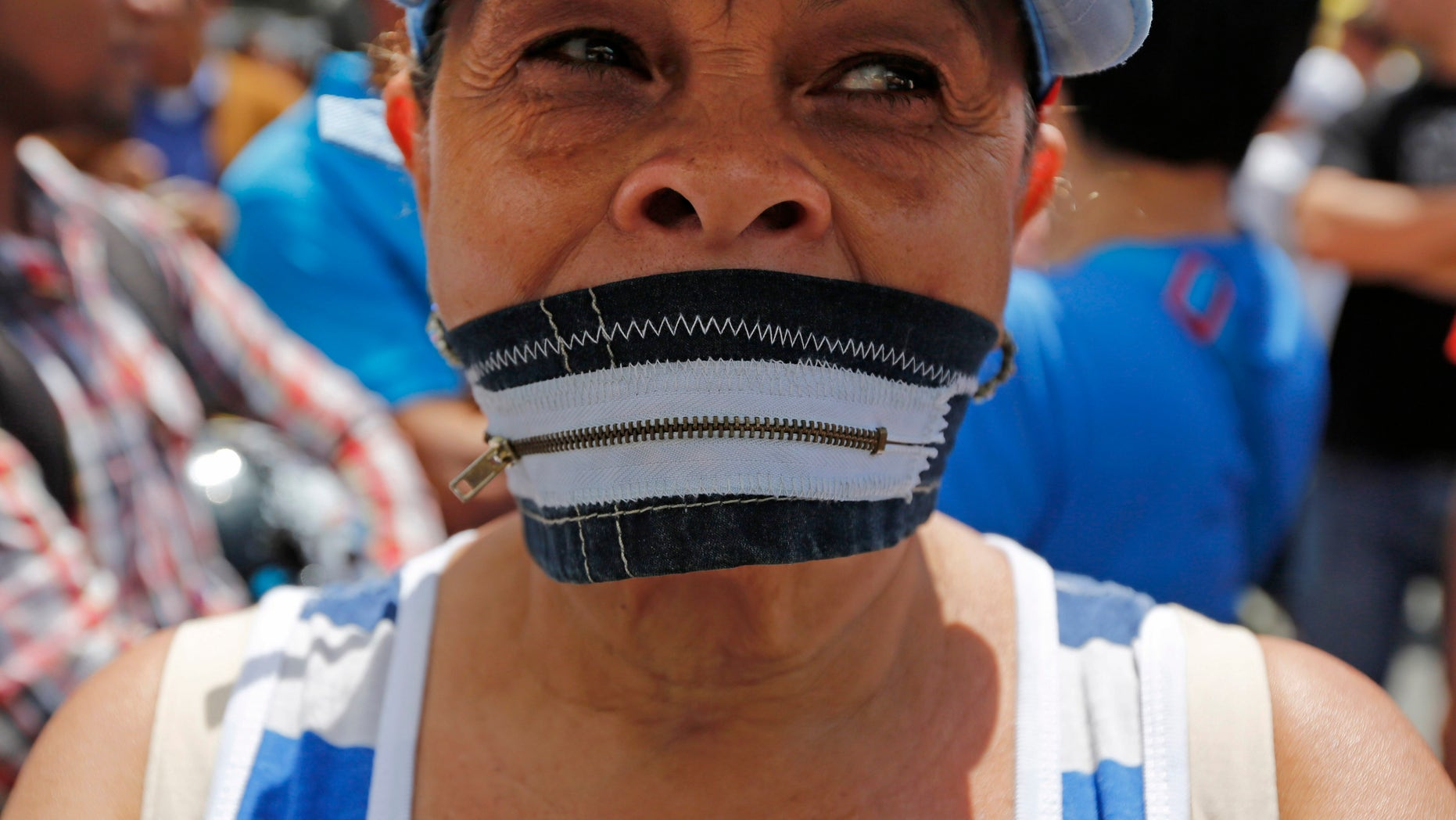 A protester wears a zipper over her mouth at a demonstration demanding the release of Metropolitan Mayor Antonio Ledezma in Caracas, Venezuela, Friday, Feb. 20, 2015. Demonstrators are condemning last night's surprise arrest of the Caracas' mayor for allegedly plotting to overthrow the government of President Nicolas Maduro. Late Thursday Maduro said that Ledezma, one of the most vocal opposition leaders, would be punished for trying to sow unrest in Venezuela. (AP Photo/Ariana Cubillos)