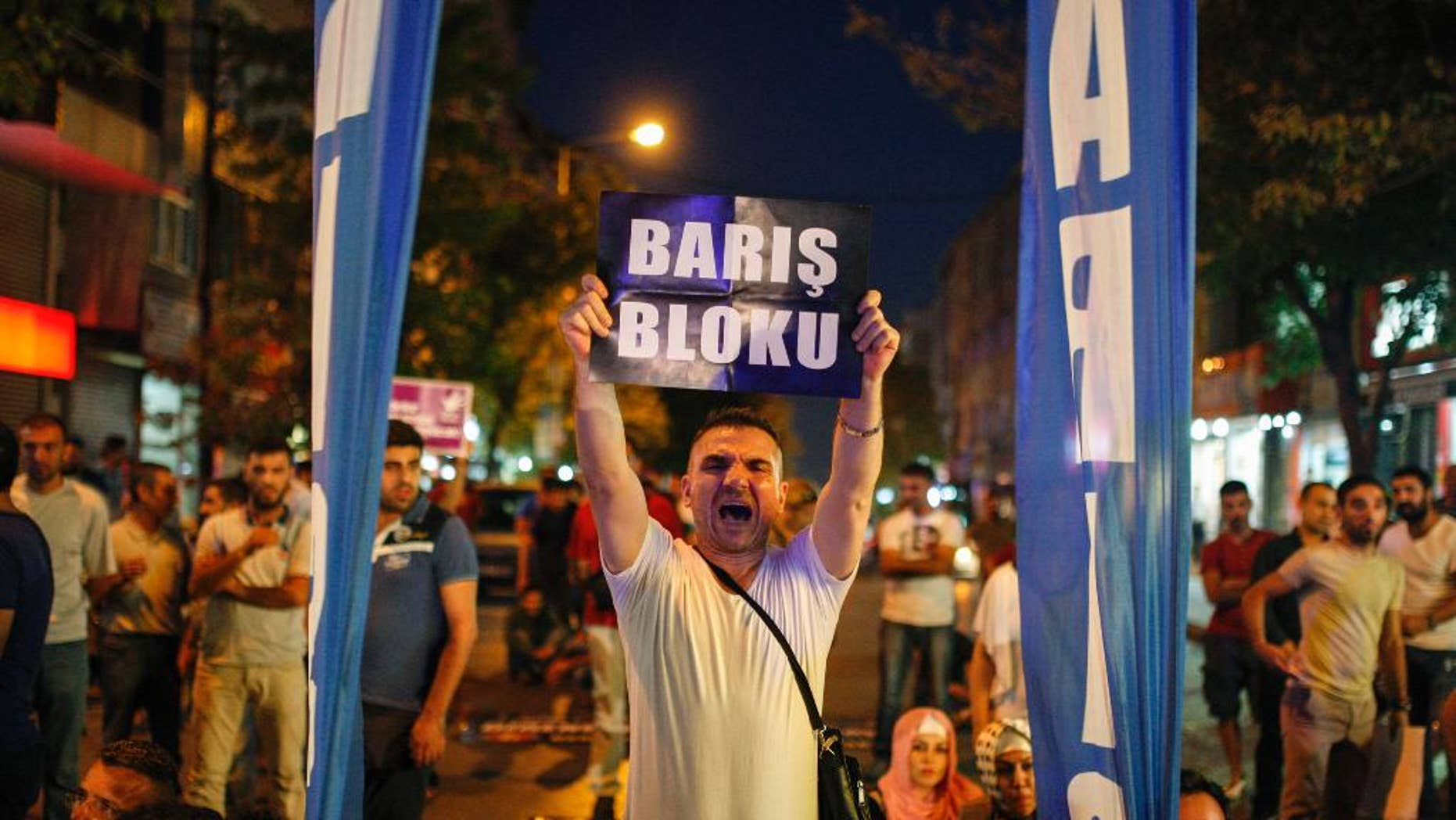 """A man protesting against Turkey's operations against Kurdish militants holds a sign that reads in Turkish: """"Peace Block"""" , in Istanbul, Wednesday, Aug. 19, 2015. There has been a sharp escalation of violence between Turkey's security forces and the Kurdistan Workers' Party, or PKK, along with the collapse of a two-year peace process with the rebels. Dozens of people, mostly Turkish soldiers, have died since July in the renewed violence. (AP Photo/Cagdas Erdogan) TURKEY OUT"""
