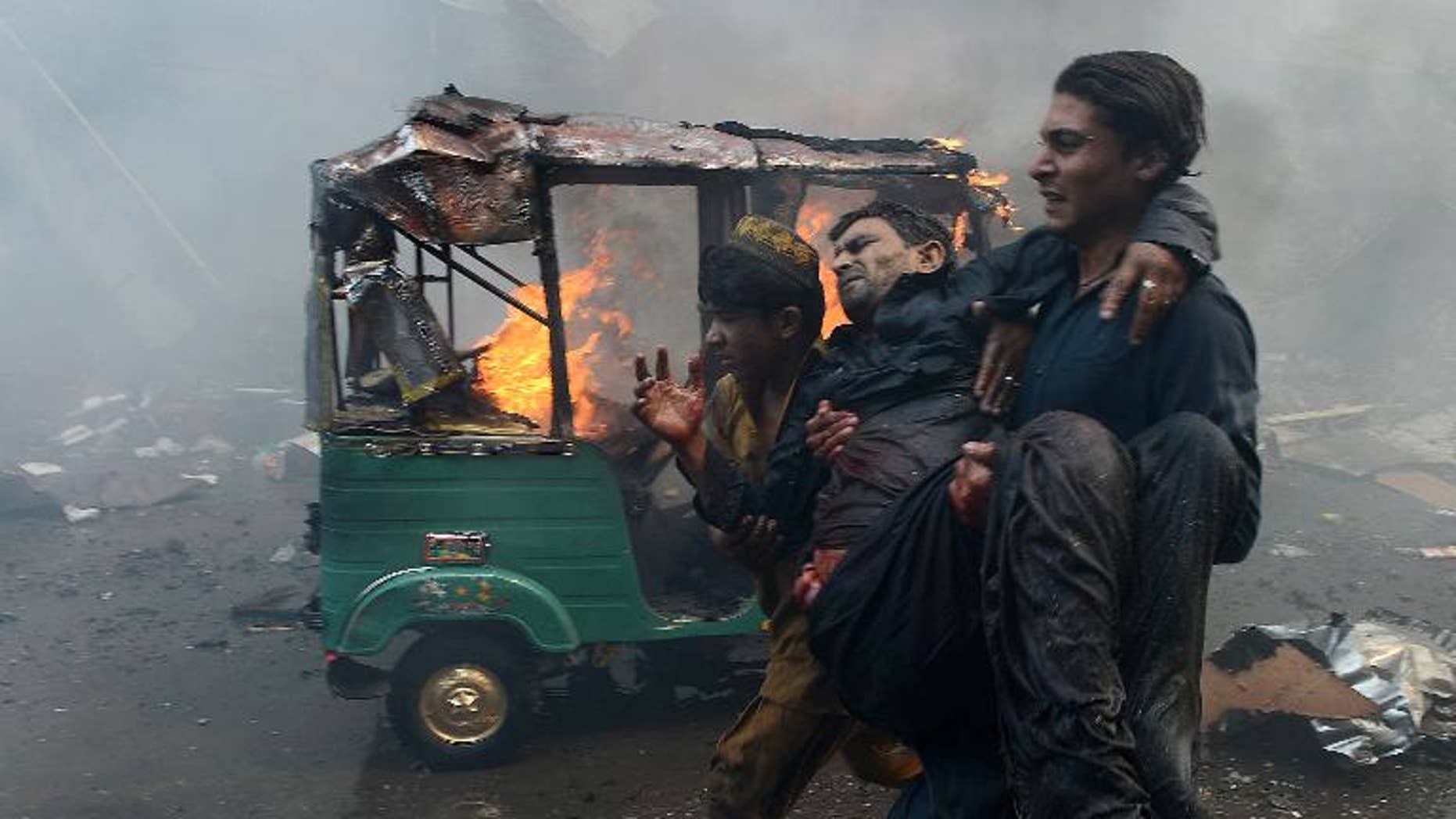 Pakistani men carry an injured blast victim at the site of a bomb explosion in the busy Kissa Khwani market in Peshawar on September 29, 2013