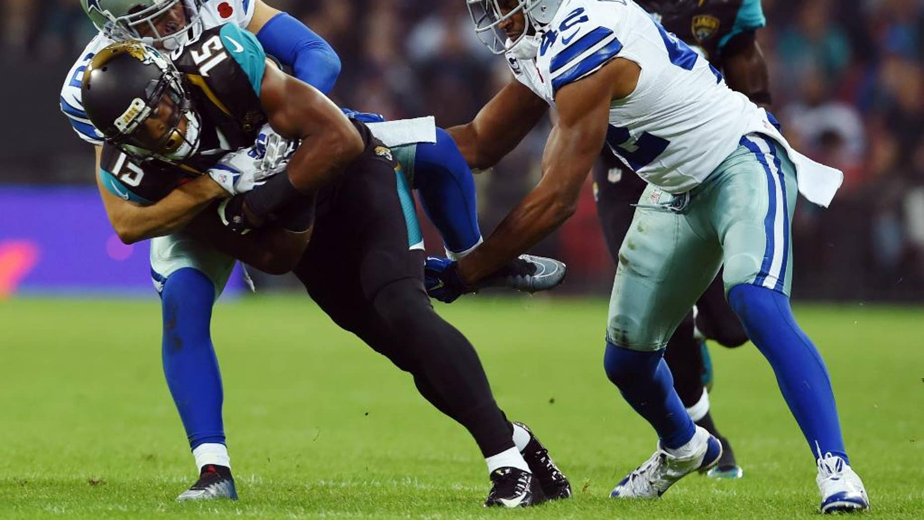 Jacksonville Jaguars wide receiver Allen Robinson (15) is tackled by Dallas Cowboys defensive back Sterling Moore (26) and strong safety Barry Church (42) during the first half of an NFL football game at Wembley Stadium, London, Sunday, Nov. 9, 2014.  (AP Photo/Matt Dunham)