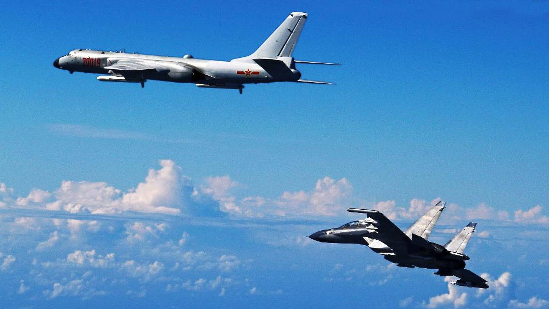 FILE - In this Sept. 25, 2016 file photo released by Xinhua News Agency, Chinese People's Liberation Army Air Force Su-30 fighter, right, flies along with a H-6K bomber as they take part in a drill near the East China Sea. China patrolled the waters of a series of hotly contested islands on Sunday, Dec. 11, 2016, a day after staging a flyover of two strategically important waterways near Taiwan and Japan. (Shao Jing/Xinhua via AP, File)