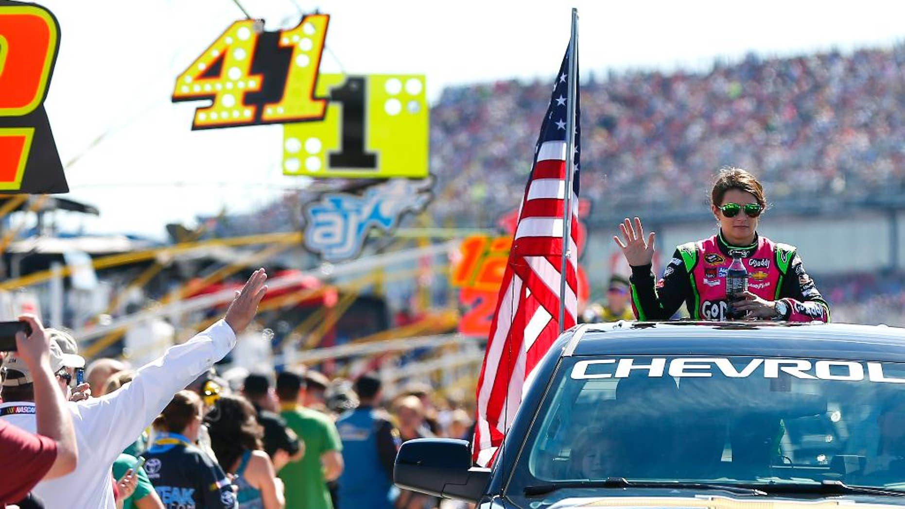 Danica Patrick, right, waves to fans as she rides in a truck to her car for the NASCAR Sprint Cup Series auto race at Talladega Superspeedway, Sunday, Oct. 19, 2014, in Talladega, Ala. (AP Photo/John Bazemore)