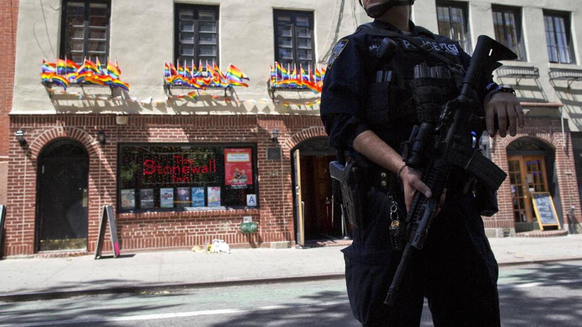 FILE - In a June 12, 2016 file photo, an armed police officer stands guard outside the Stonewall Inn, in New York. Sunday's mass shooting the Pulse nightclub, in which gunman Omar Mateen killed dozens of people before dying in a gun battle, prompted an outpouring of reminiscence and reflection on that vital roles that such clubs have played for many lesbians, gays, bisexuals and transgender people across the U.S. (AP Photo/Mary Altaffer, File)