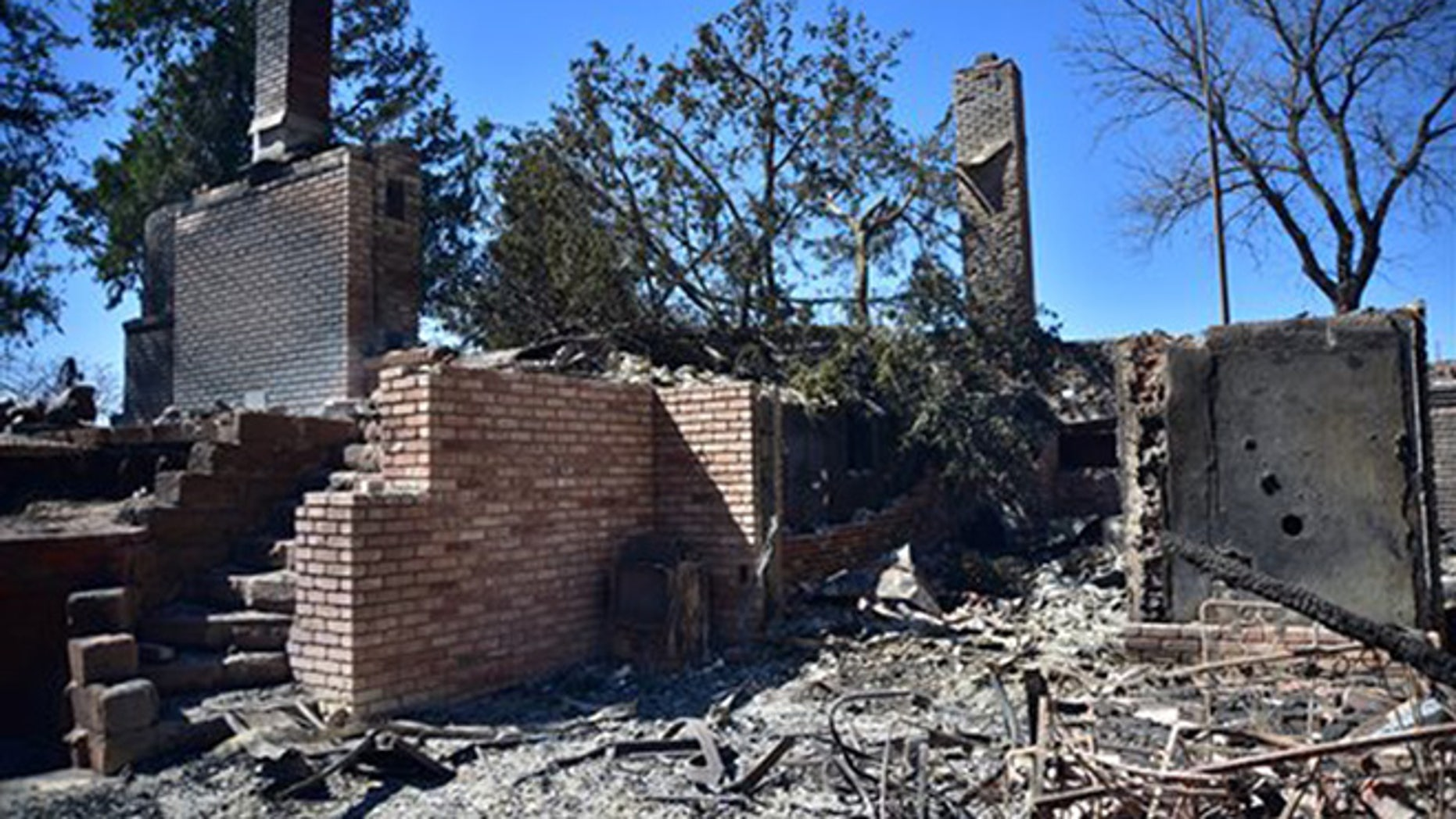 Fire damage to a home Thursday, March 24, 2016 near Medicine Lodge, Kan. A fire that started Tuesday in Oklahoma has now burnt near 400, 000 acres in Kansas and Oklahoma. (Andrew Whitaker/ The Hutchinson News via AP)
