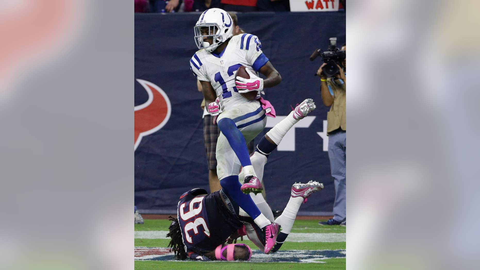 Indianapolis Colts' T.Y. Hilton (13) catches a pass for a touchdown as Houston Texans' D.J. Swearinger (36) defends the play during the second half of an NFL football game, Thursday, Oct. 9, 2014, in Houston. (AP Photo/David J. Phillip)