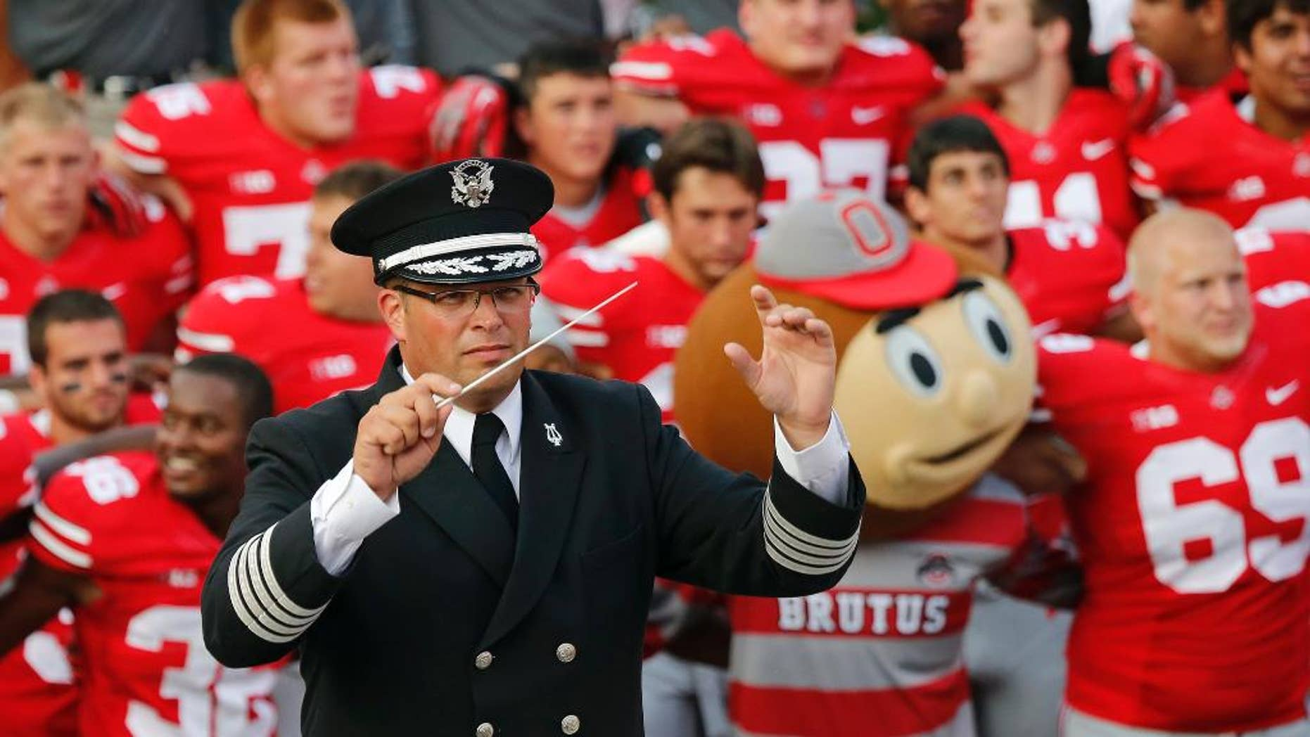 """FILE - In this Sept. 7, 2013 file photo, Ohio State University marching band director Jonathan Waters leads the band in """"Carmen Ohio"""" following a NCAA football game against San Diego State at Ohio Stadium in Columbus, Ohio. Ohio State officials say there is no recent record of campus police attending an annual ritual where marching band members entered Ohio Stadium in their underwear. The Midnight Ramps were cited in an investigation into the band's """"sexualized culture"""" that resulted in Waters' July 24 firing. (AP Photo/The Columbus Dispatch, Adam Cairns, File)"""