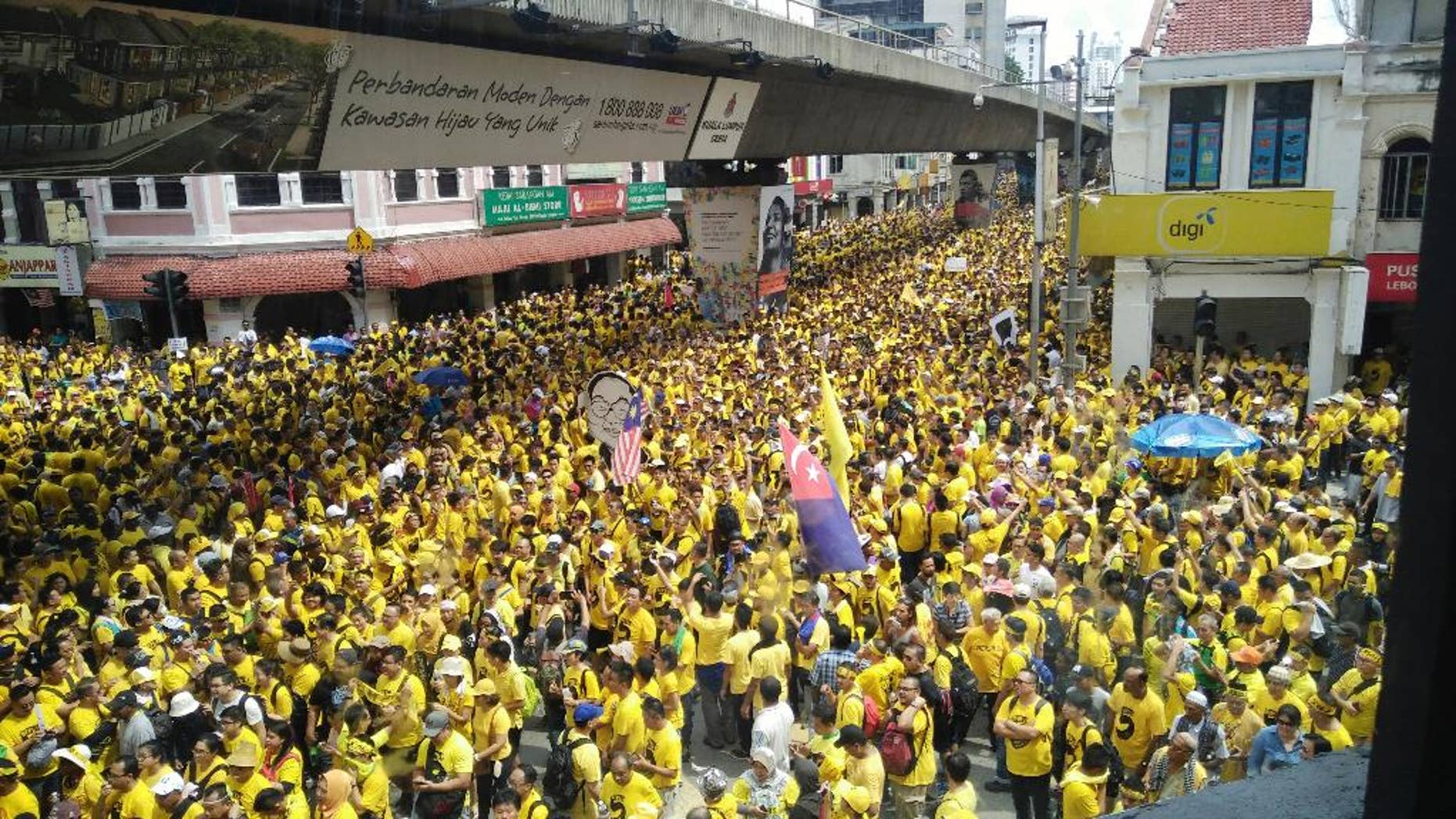 Protesters occupy a street during a rally in downtown Kuala Lumpur, Malaysia, Saturday, Nov. 19, 2016. Tens of thousands of yellow-shirt protesters rallied Saturday in Kuala Lumpur seeking Malaysian Prime Minister Najib Razak's resignation over a financial scandal, undeterred by a police ban and the arrest of more than a dozen activists. (AP Photo/Forest Chew)