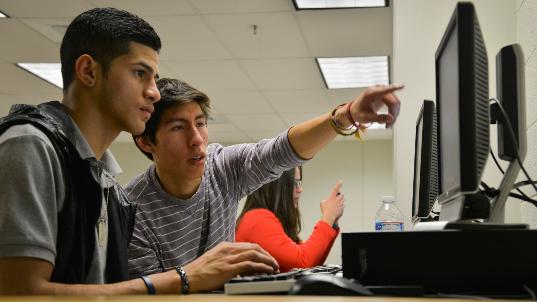 ARLINGTON, VA - JANUARY 23:Rommel Romano, L, a Washington Lee High School student, gets help writing his college essay from volunteer Rodrigo Ventiades as high school students who are undocumented immigrants receive help writing college essays and scholarship applications from volunteer mentors at Washington Lee High School on Thursday, January 23, 2014, in Arlington, VA.  The Dream Project is an Arlington-based organization that provide mentoring and scholarships to undocumented high school graduates who want to attend college but in many states - including Virginia - do not qualify for in-state tuition.  Ventiades is from Bolivia and Romano is half Dominican Republican/half Salvadorian.  (Photo by Jahi Chikwendiu/The Washington Post via Getty Images)
