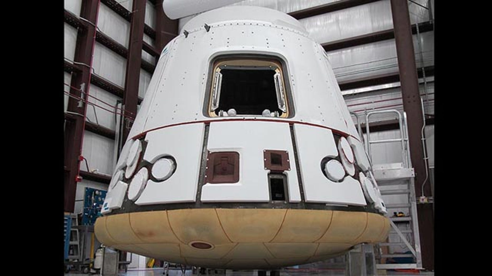 In the SpaceX hangar at Cape Canaveral, the Dragon spacecraft prepares for integration with the Falcon 9 launch vehicle. Visible at the base of the spacecraft is Dragon�s heat shield, made of PICA-X, the SpaceX manufactured variation on NASA�s Phenolic Impregnated Carbon Ablator (PICA) heat shield material. Dragon will reenter the Earth�s atmosphere at around 7 kilometers per second (15,660 miles per hour), heating the exterior up to 1850 degrees Celsius. However, just a few inches of the PICA-X material will keep the interior of the spacecraft at a comfortable temperature.