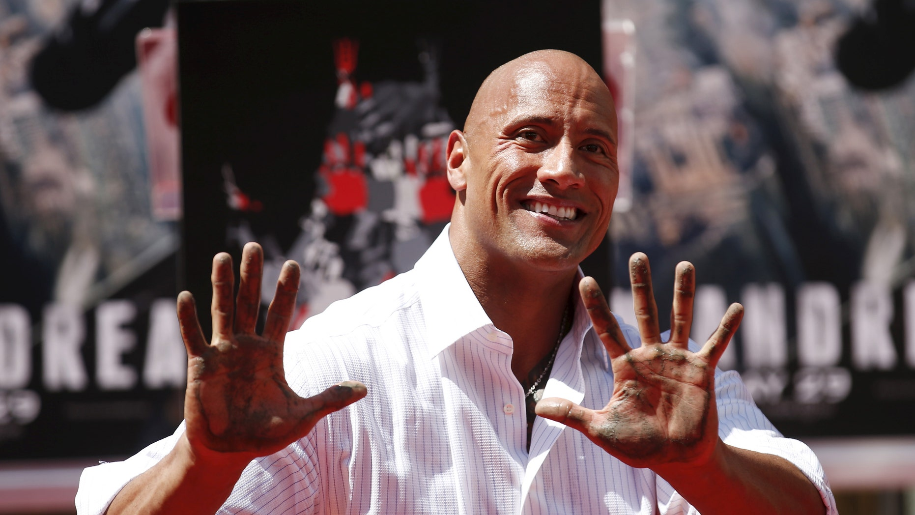 """File photo - Actor Dwayne """"The Rock"""" Johnson poses after putting his hands in cement during his hand and footprints ceremony in the forecourt of the TCL Chinese Theatre in celebration of his movie """"San Andreas,"""" in Hollywood, Calif. May 19, 2015. (REUTERS/Danny Moloshok)"""