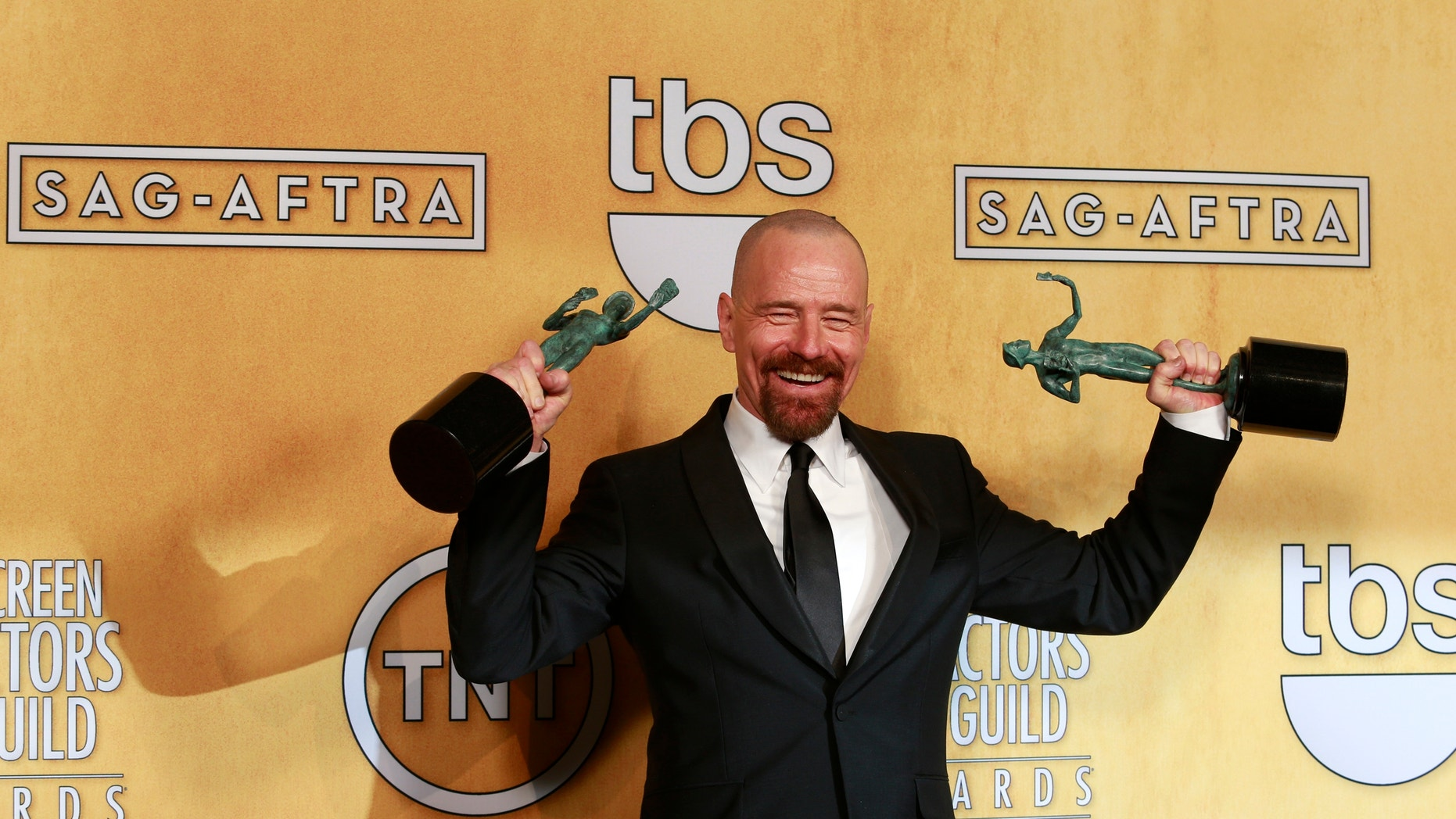 """Bryan Cranston poses backstage with his awards for outstanding male actor in a drama series for """"Breaking Bad"""" and for outstanding cast in a motion picture for """"Argo"""" at the 19th annual Screen Actors Guild Awards in Los Angeles, California January 27, 2013."""