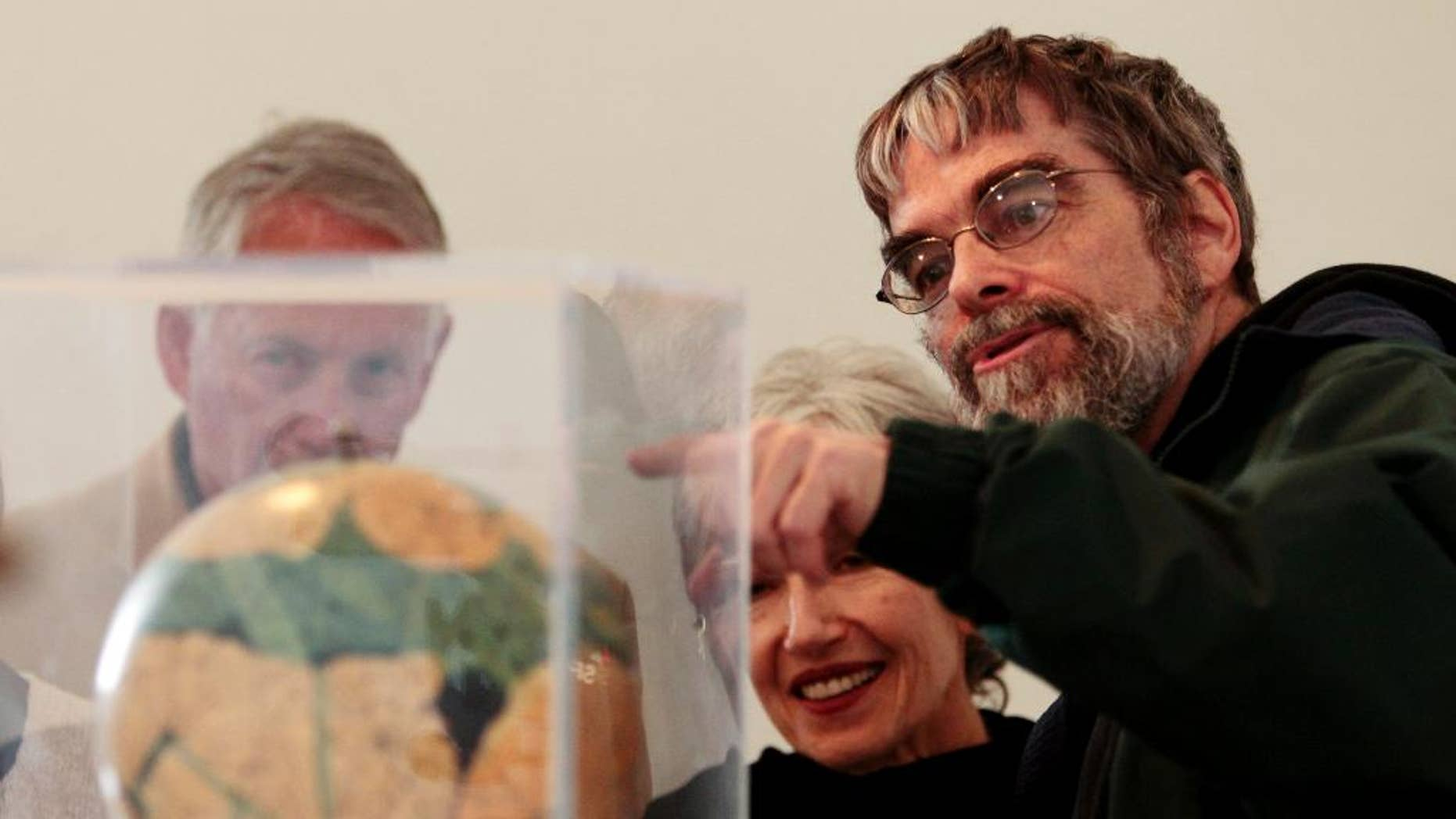 FILE - In this April 15, 2011 file photo, Brother Guy Consolmagno, a Jesuit astronomer at the Vatican's Observatory, right, shows to visitors the Globe of planet Mars from the collection of the Specola Vaticana. The Vatican Observatory has invited leading scientists and cosmologists to talk black holes, gravitational waves and space-time singularities as it honors Monsignor George Lemaire, a Jesuit cosmologist considered one of the fathers of the idea that the universe began with a gigantic explosion. (AP Photo/Gregorio Borgia)