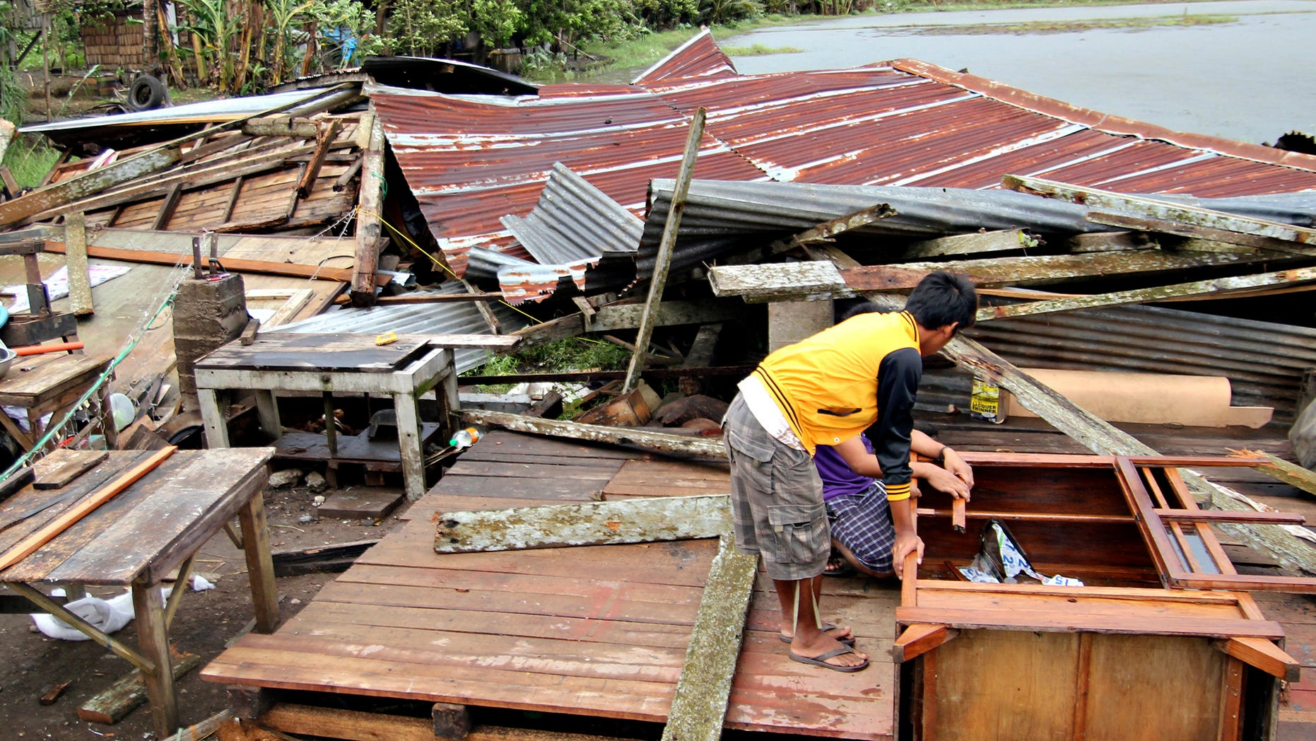 Dec. 4, 2012: Residents prepare to assess their house which was damaged by Typhoon Bopha in Butuan city in southeastern Philippines.