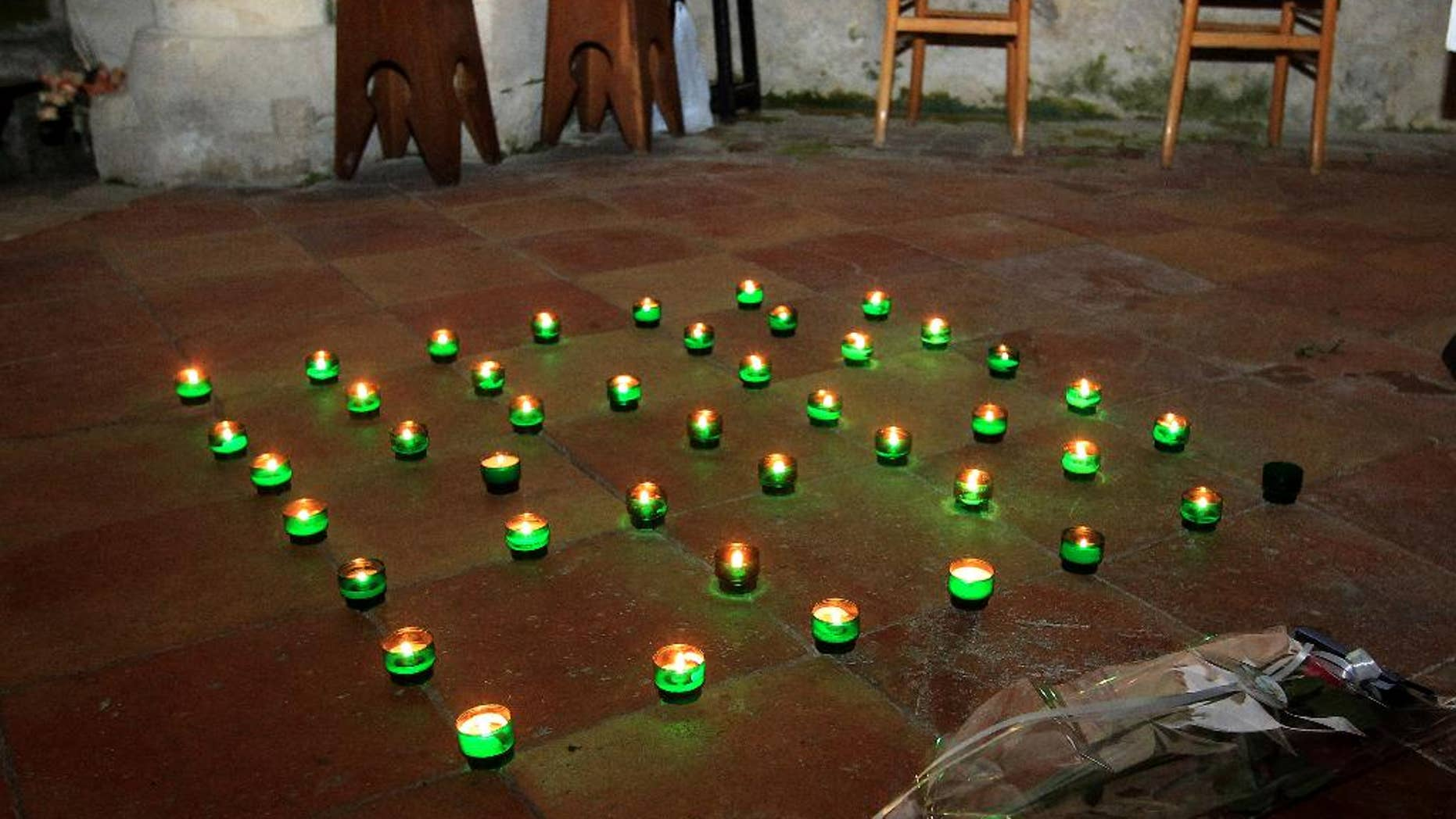Candles and a bunch of flowers are placed on the ground inside a church in Petit-Palais-et-Cornemps, near the crash site of Puisseguin, southwestern France, in memory of the 43 victims of a road crash, Friday, Oct. 23, 2015. A truck and a bus transporting retirees on a day trip collided and caught fire Friday on a country road in wine country in southwest France, killing 43 people and gravely injuring at least four others, authorities said. (AP Photo/Bob Edme)